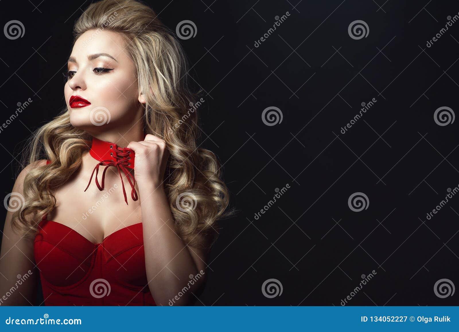 Bello modello biondo che indossa cima attaccata corsetto rosso che prova a decollare girocollo legato per prendere un respiro