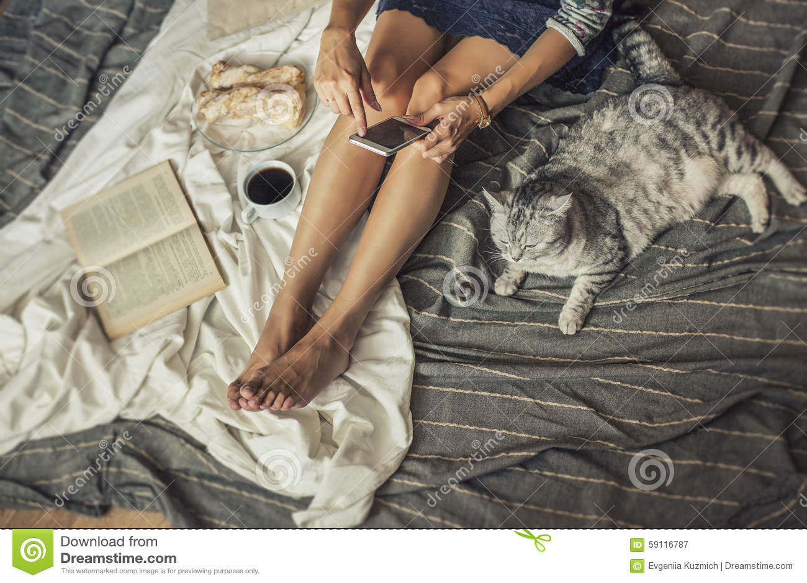 Bello modello della donna con caffè, pasticcerie, telefono domestico sulla b