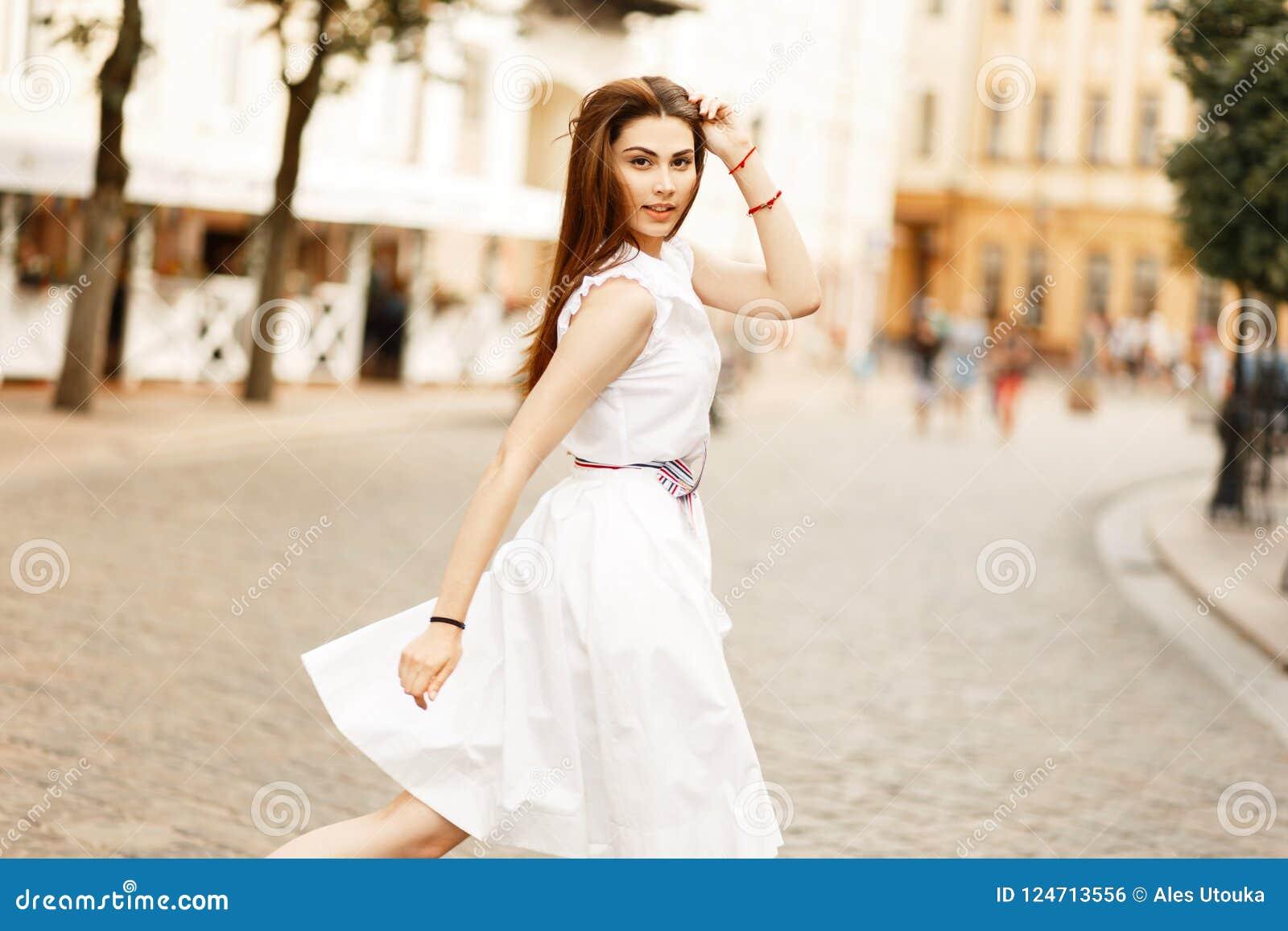 2af44593dde5 Il bello modello della giovane donna in vestito bianco alla moda sta  camminando sulla via e sta esaminando la macchina fotografica