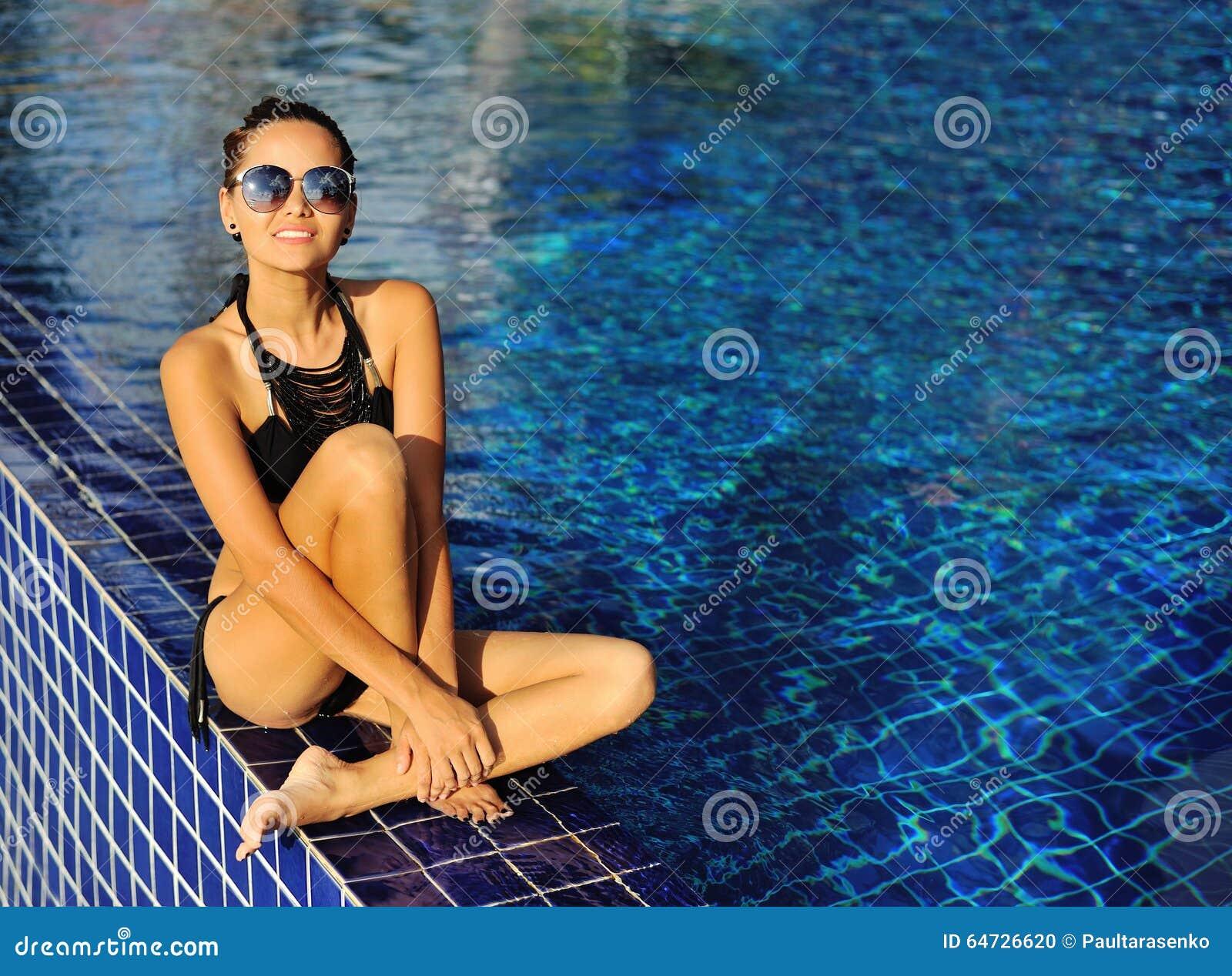 Bello modello femminile felice che posa dallo stagno, estate all aperto