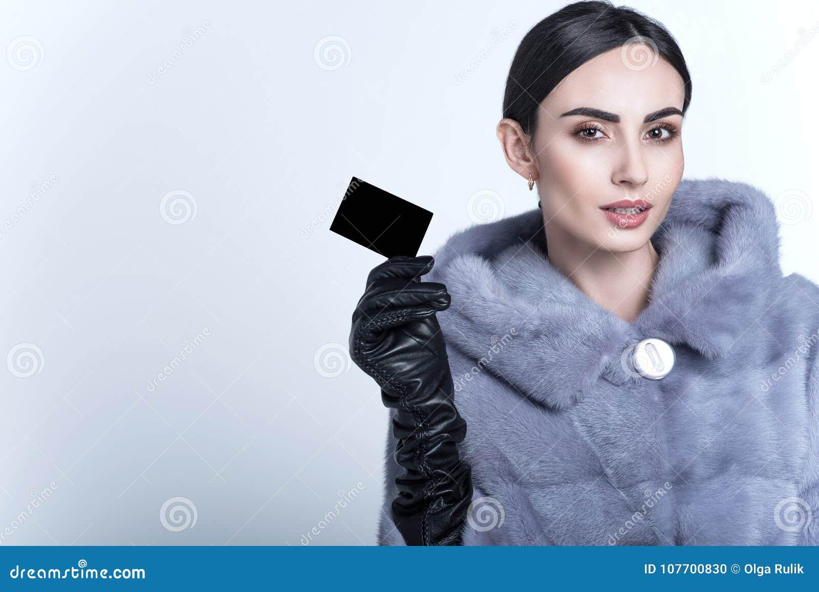 Bello modello sorridente che indossa la pelliccia blu del visone ed i guanti di cuoio lunghi che tengono biglietto da visita in b
