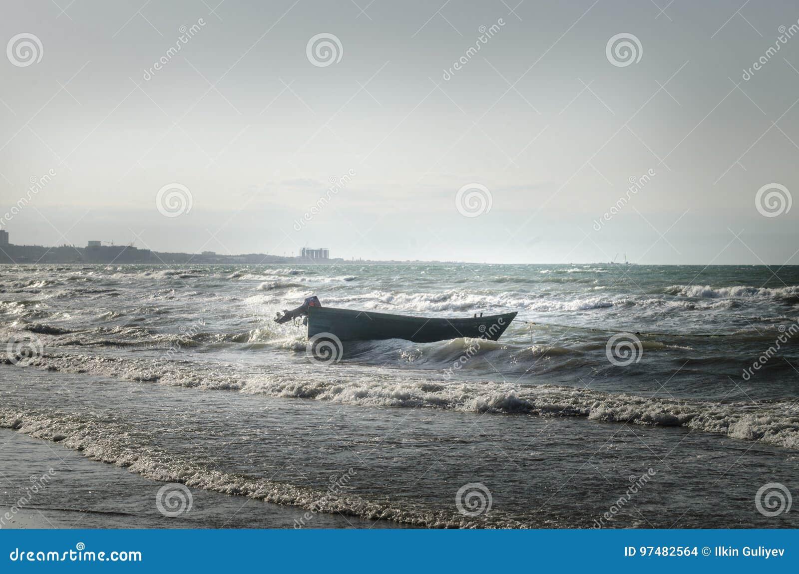 Bello paesaggio della barca sulla spiaggia in tempo nuvoloso Barca d annata nella spiaggia l azerbaijan