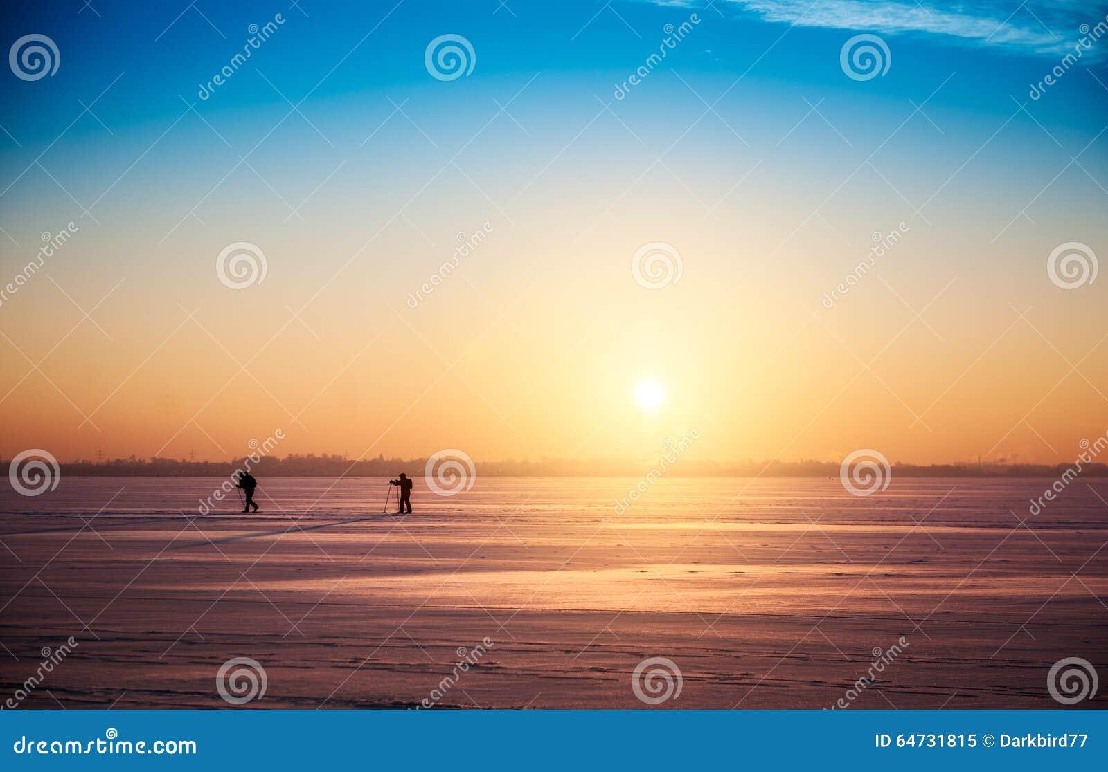 Bello paesaggio di tramonto di inverno con gli sciatori che attraversano il pæse