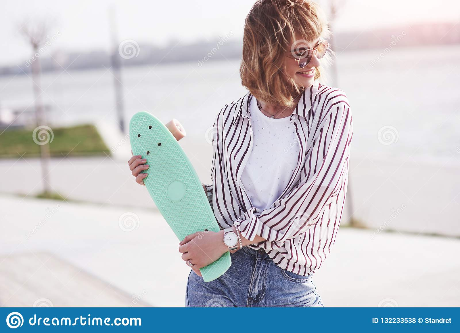 Bello pattinatore femminile teenager che si siede sulla rampa al parco del pattino Concetto delle attività urbane di estate