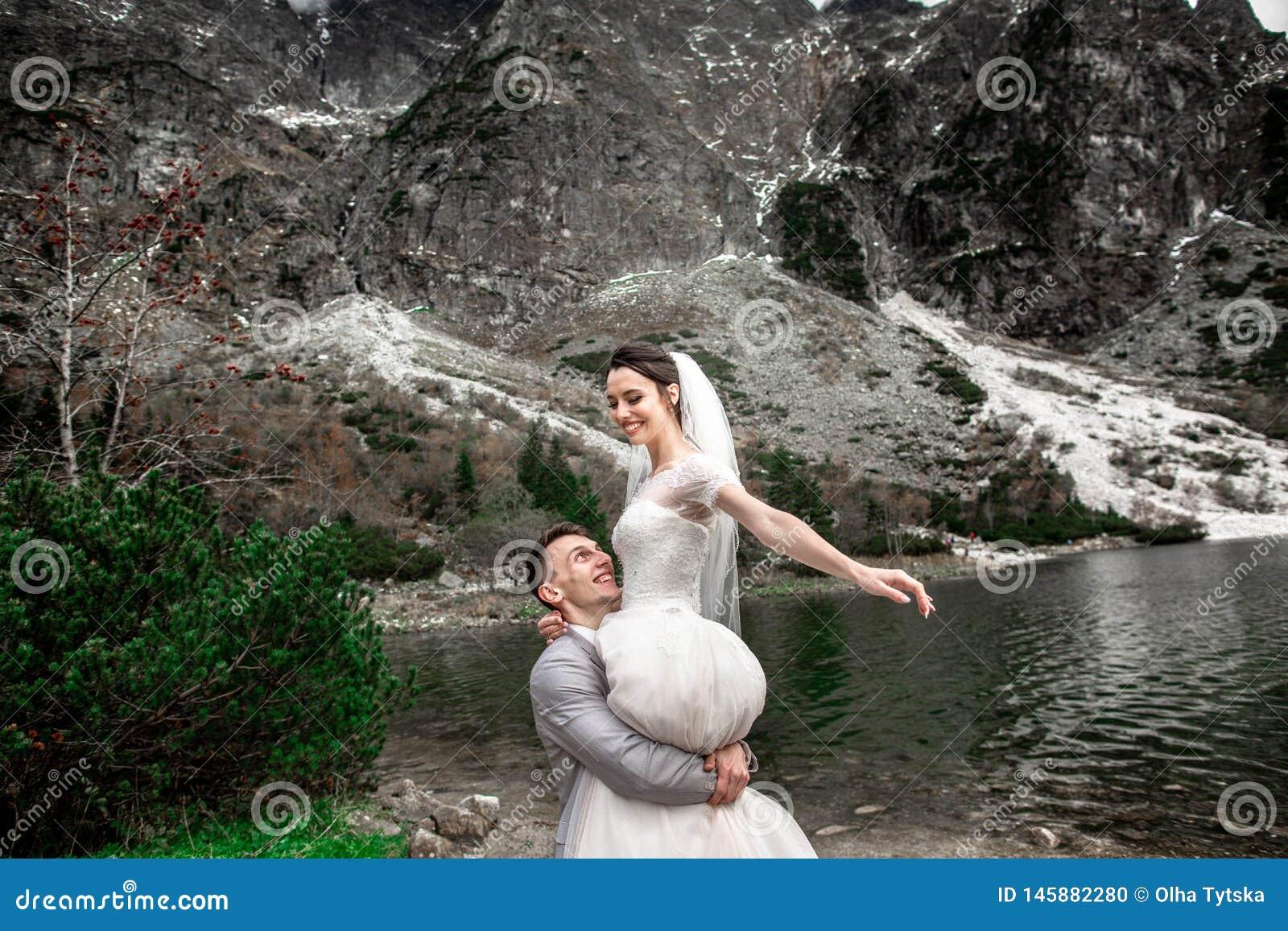 Bello photosession di nozze Lo sposo circonda la sua giovane sposa, sulla riva del lago Morskie Oko poland