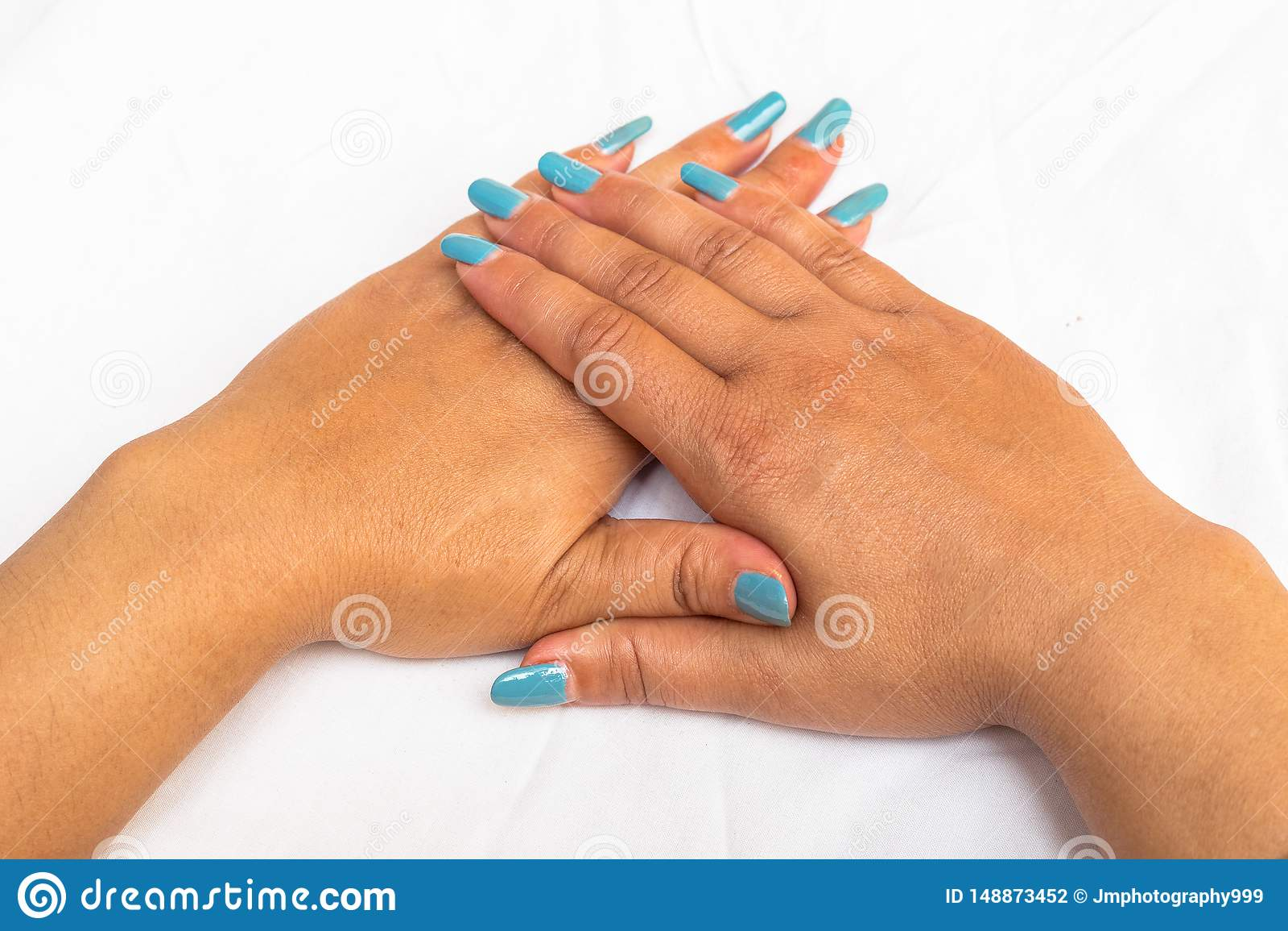 Bello primo piano delle mani di una giovane donna con il manicure blu lungo sulle unghie
