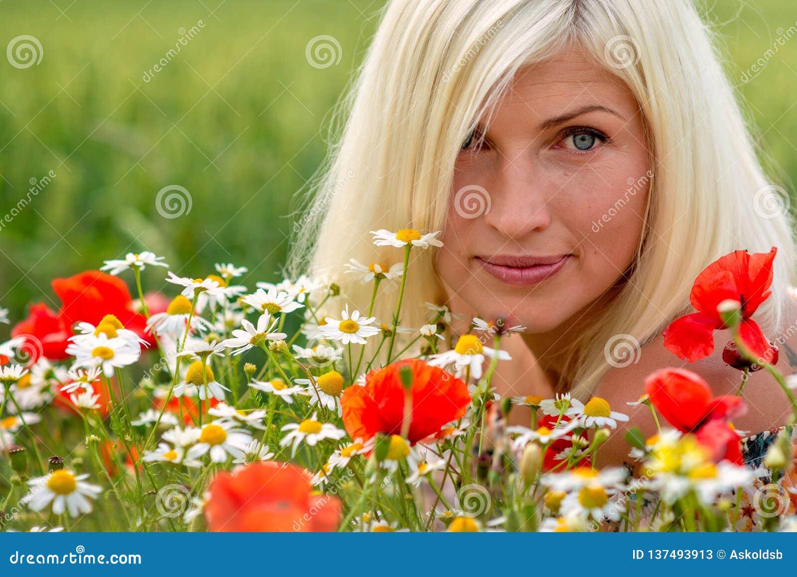 Bello, ritratto attraente e biondo della donna con i fiori del prato Fuoco molle