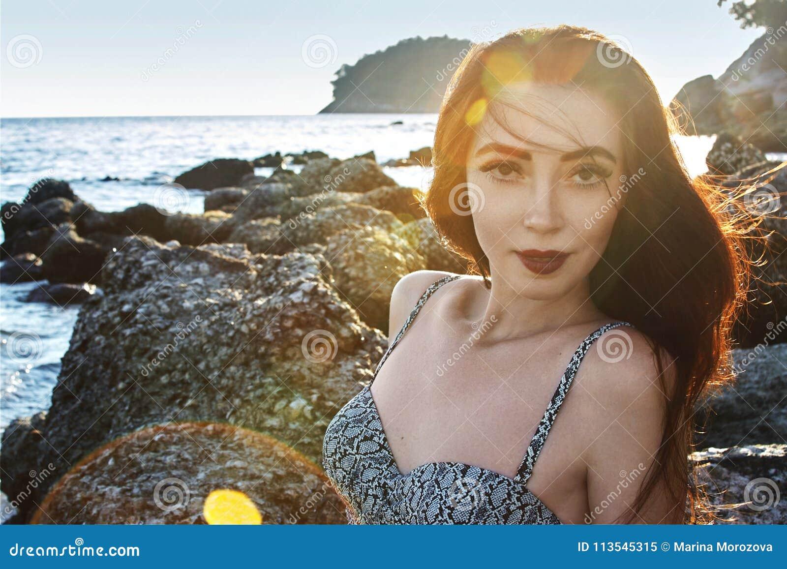 Bello ritratto della donna castana sveglia Modello di stile di Boho Modello sexy sulla spiaggia alla luce di tramonto