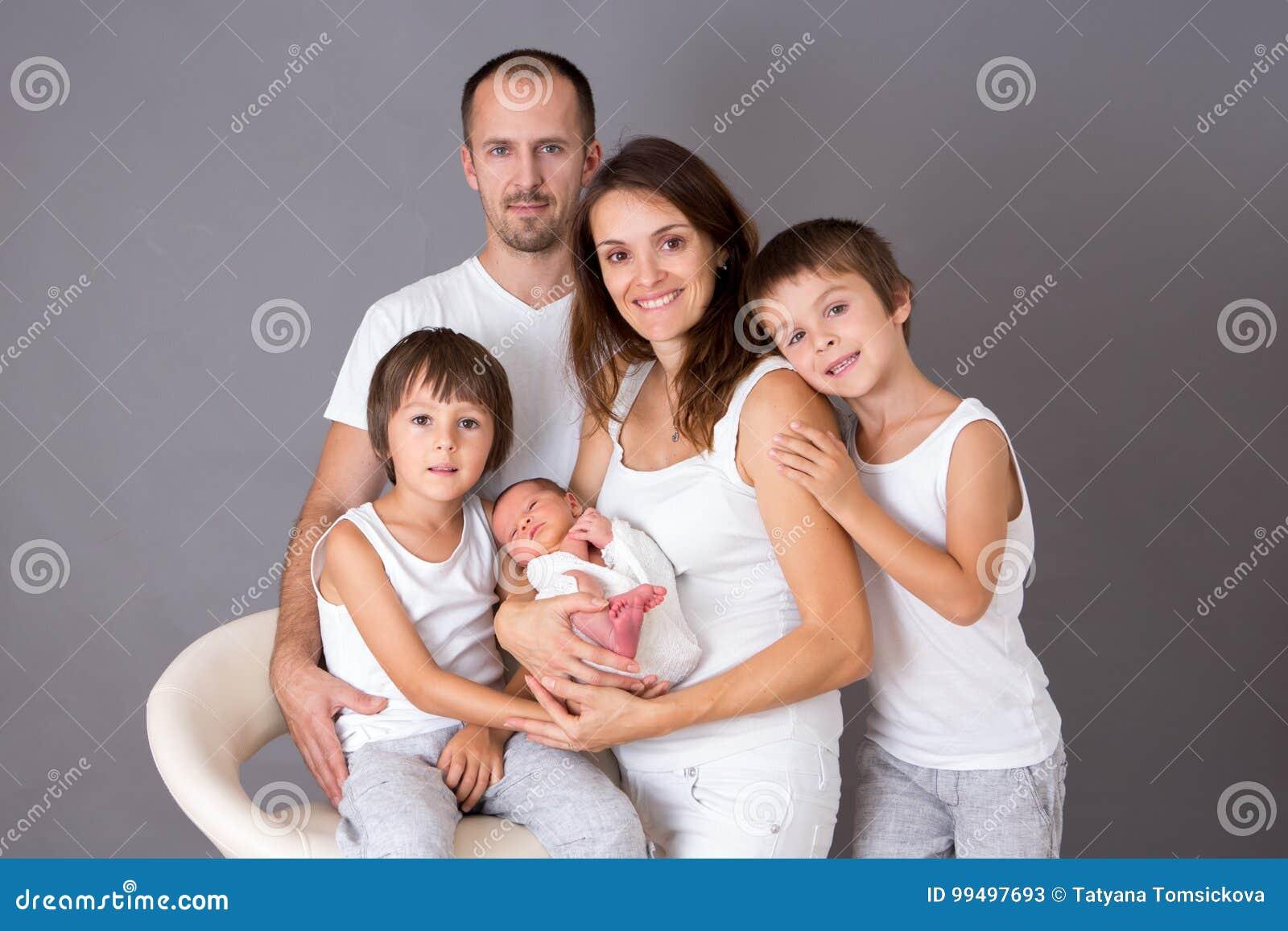 Bello ritratto della famiglia, padre, madre e tre ragazzi, lookin