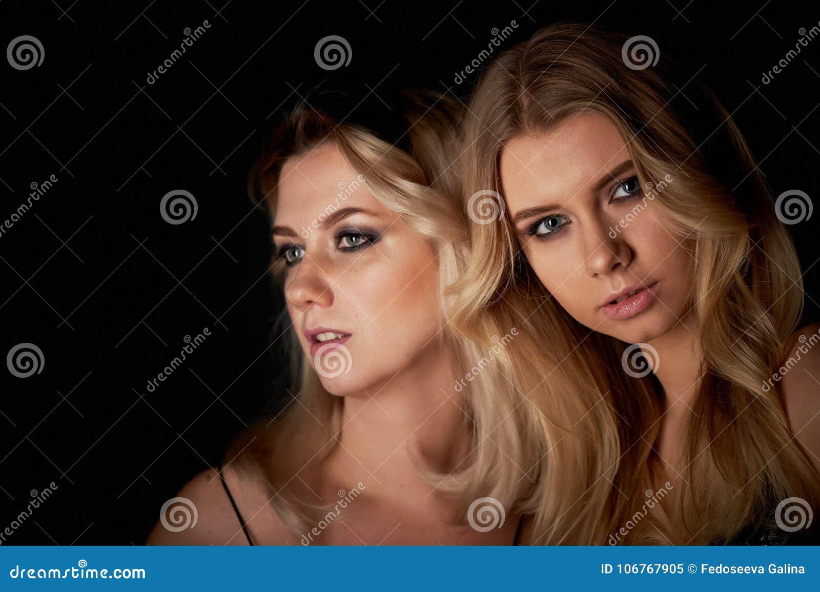 Bello ritratto della figlia e della madre in studio su fondo nero Guardi grande Trucco professionale