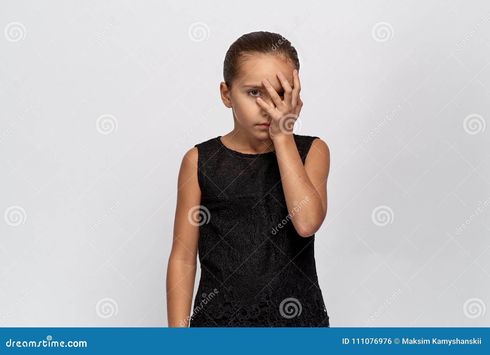 Bello ritratto di una ragazza annoiata, mezzo fronte chiuso dalla palma ragazza con capelli neri stanchi della conversazione secc