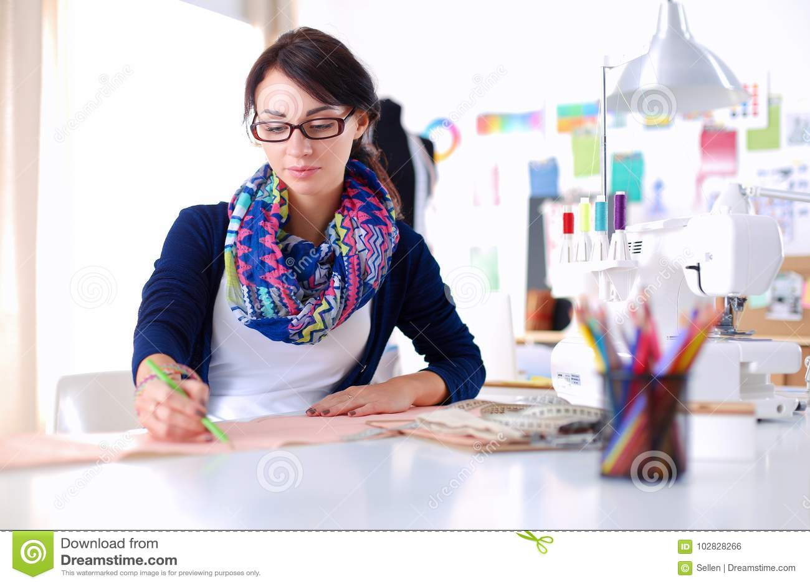 Bello stilista che si siede allo scrittorio in studio