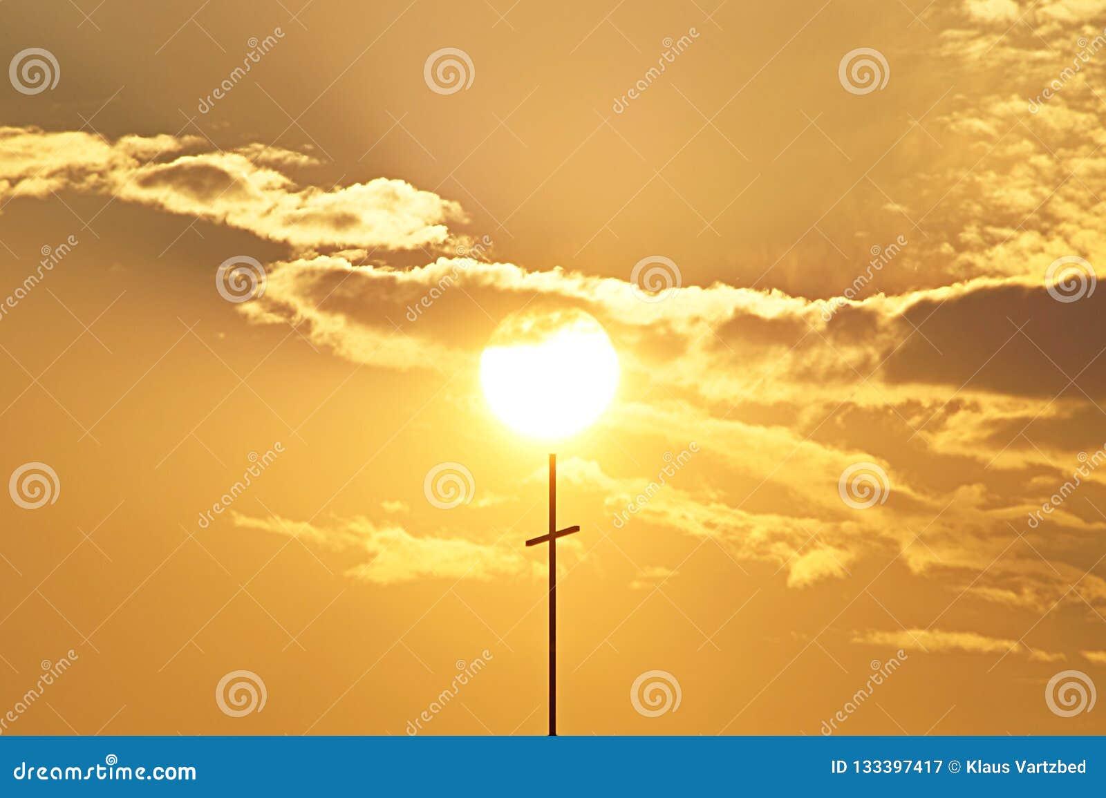 Bello tramonto attraverso le nuvole con il cattolico trasversale