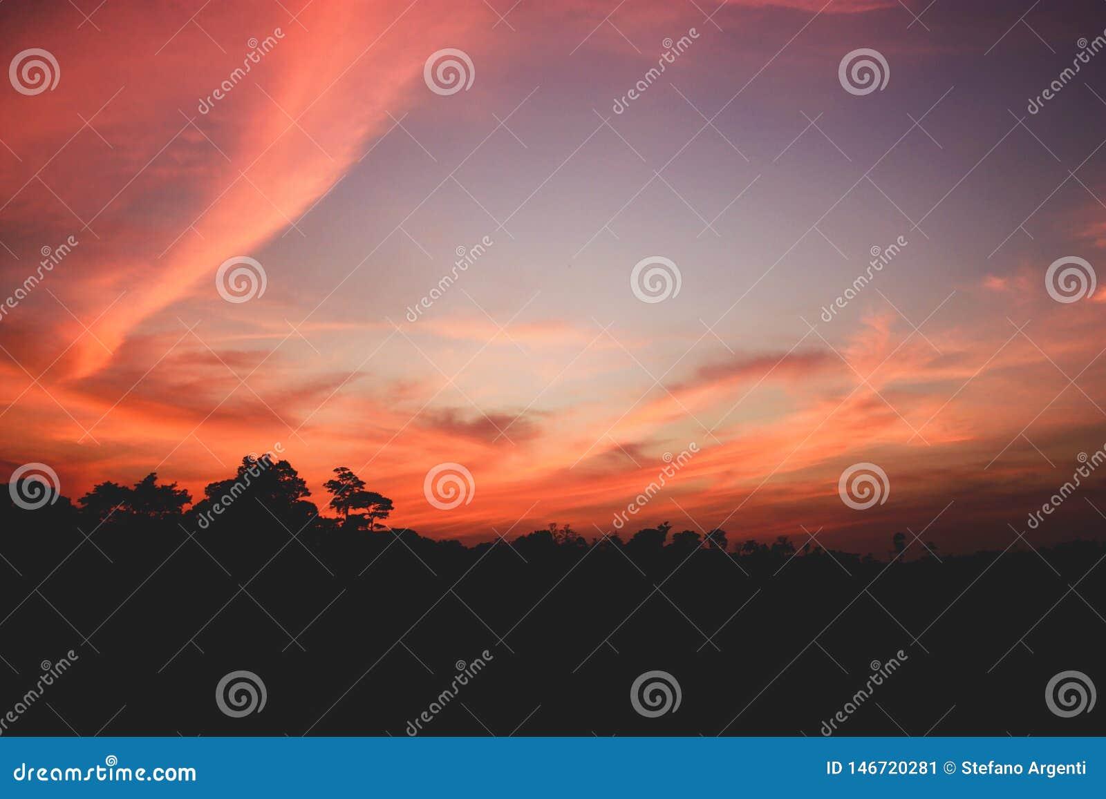 Bello tramonto con le nuvole dentellate