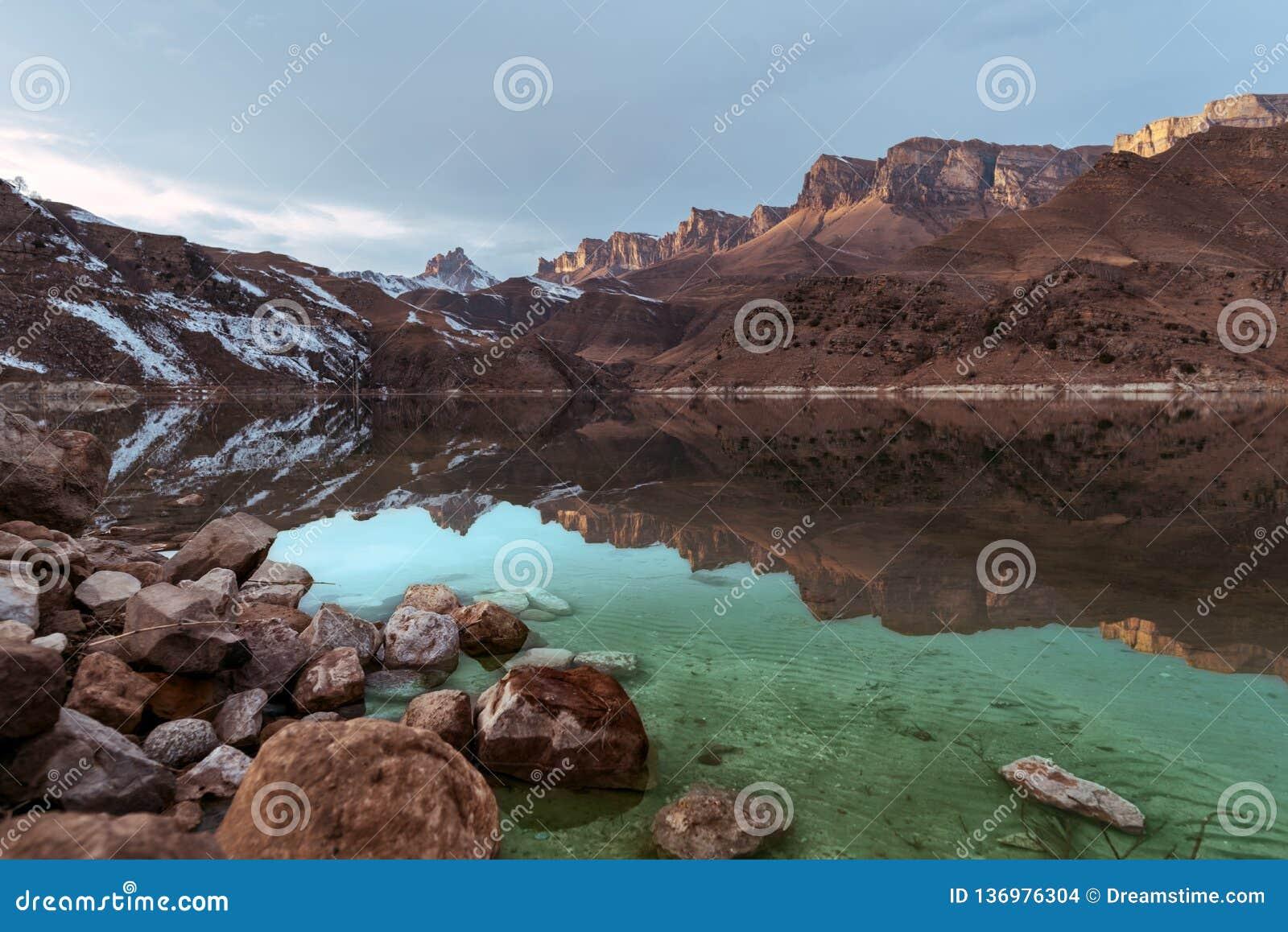 Bello tramonto nella riflessione di un lago della montagna