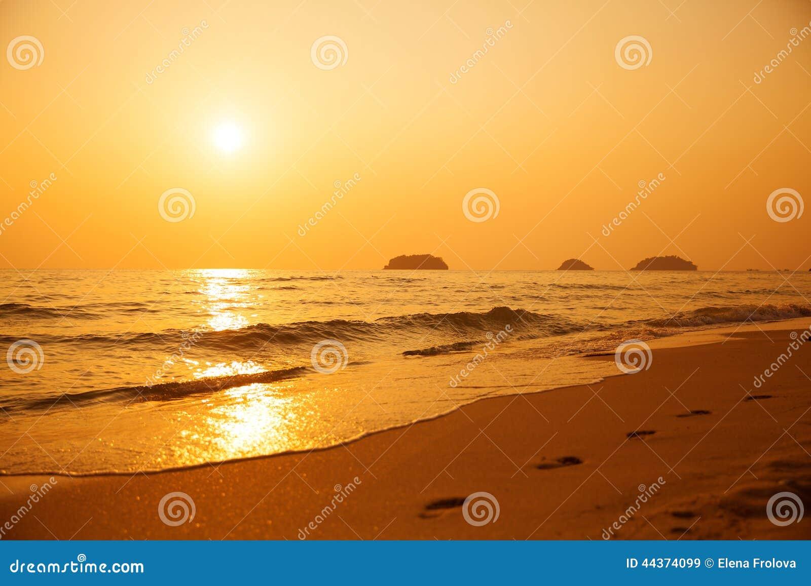 Bello tramonto sopra il mare Orme nella sabbia