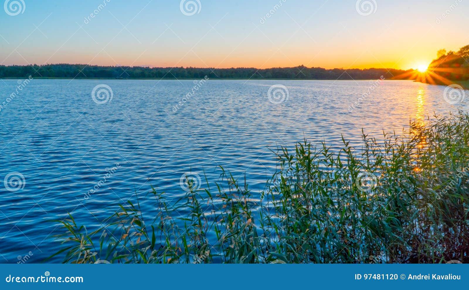 Bello tramonto sul lago, pescatori sulla barca