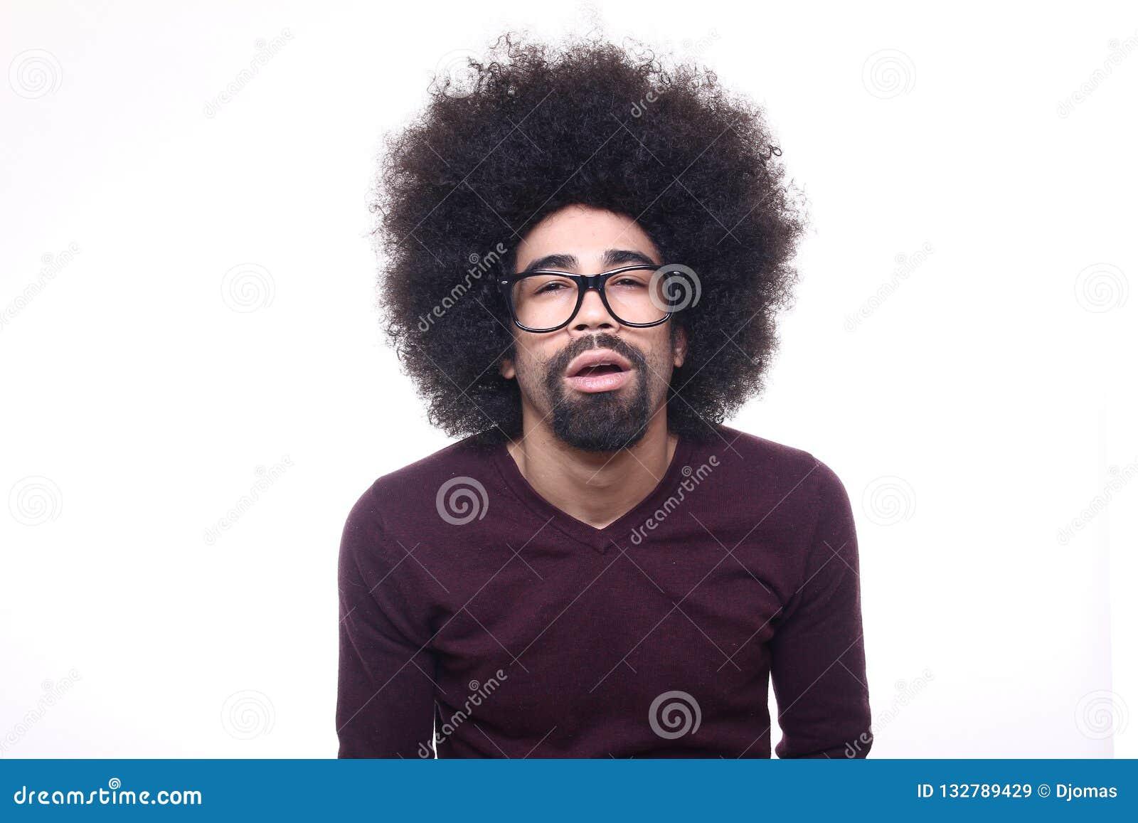 Bello uomo funky felice di afro che posa davanti ad un fondo