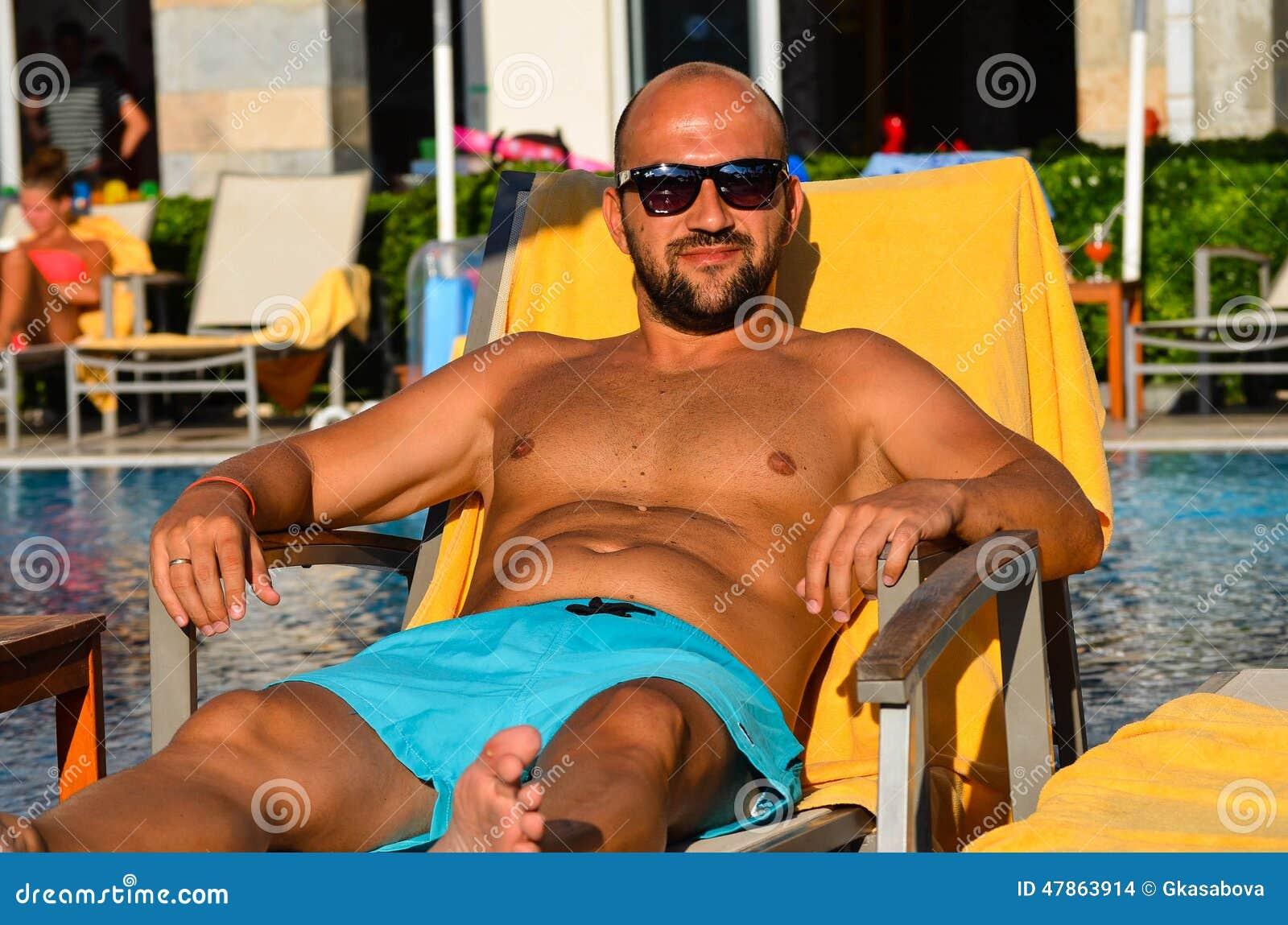 Bello uomo sorridente con gli occhiali da sole e la fede nuziale che si rilassano e che oziano allo stagno e che si divertono