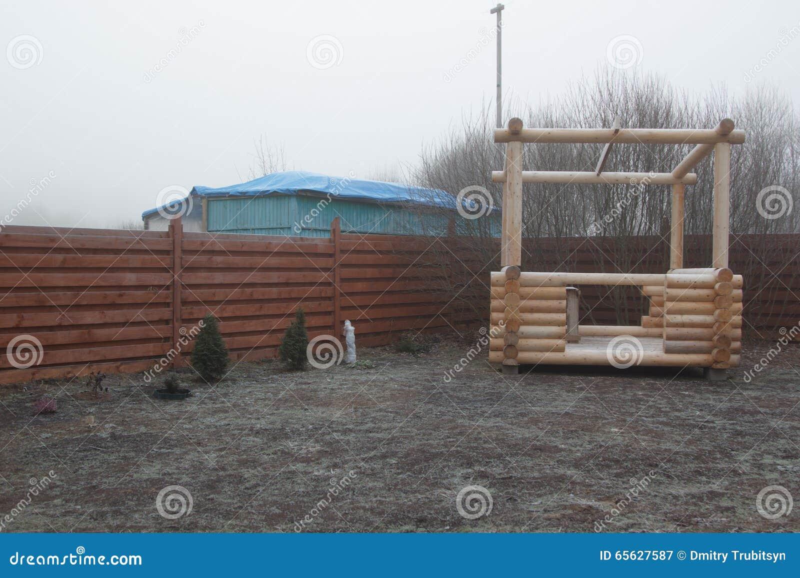 Belvédère de rondin dans le jardin congelé en brume
