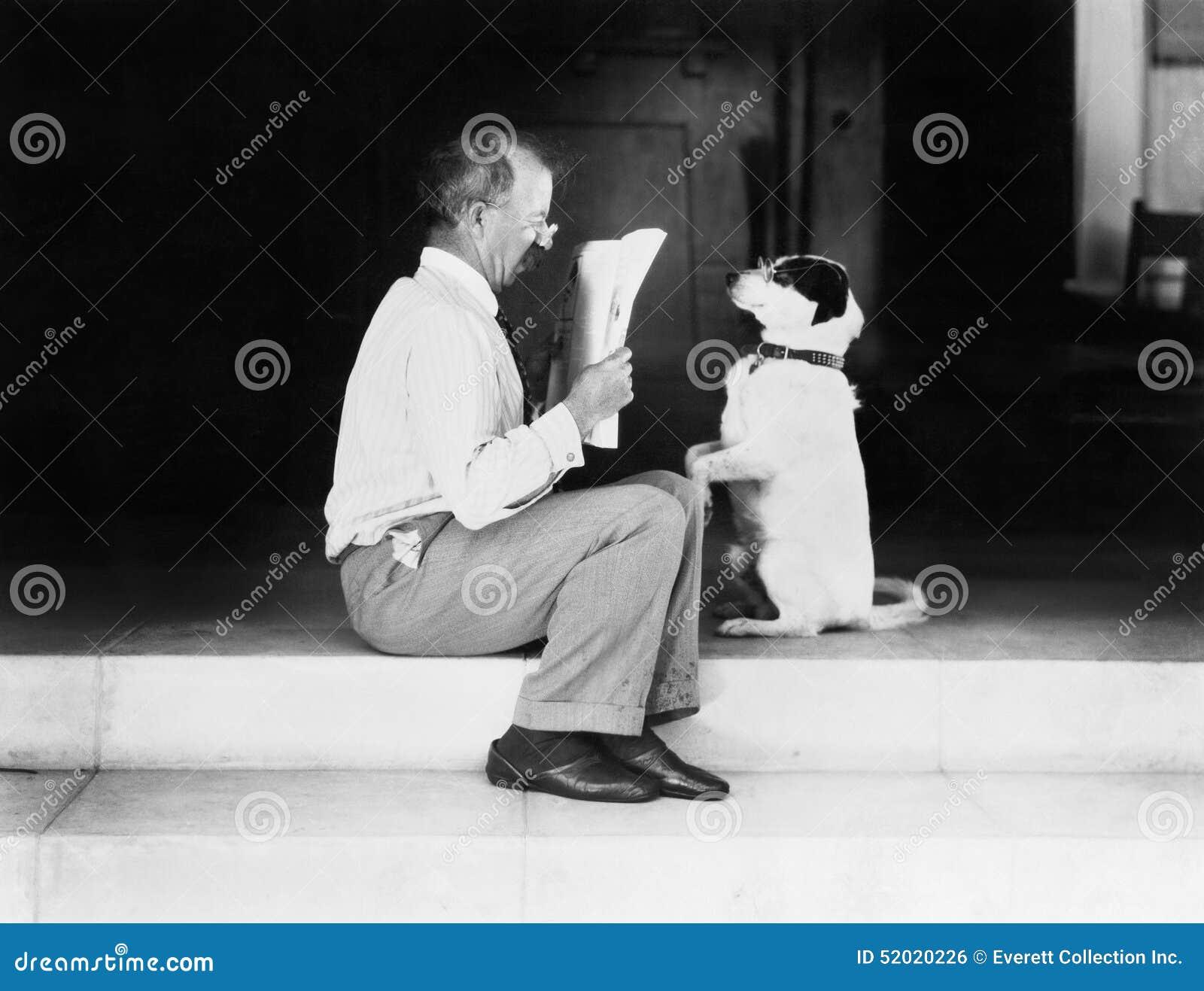 Bemannen Sie das Ablesen einer Zeitung mit seinem Hund (alle dargestellten Personen sind nicht längeres lebendes und kein Zustand