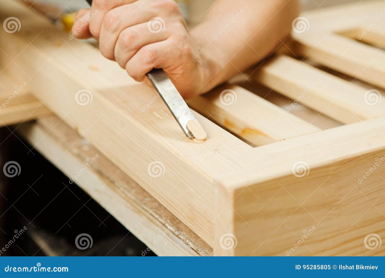 Bemannen Sie das Arbeiten mit dem Schnitzen der Ausrüstung in der Werkstatt, die Meißel hält