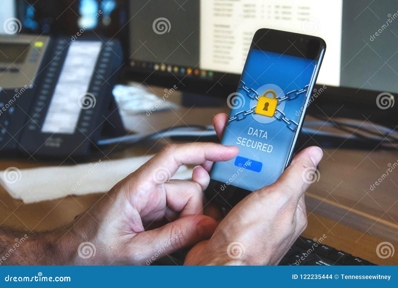 Bemannen Sie das Halten eines intelligenten Mobiltelefons mit einer Datensicherheitsanwendung, die ein gelbes Vorhängeschloß anze