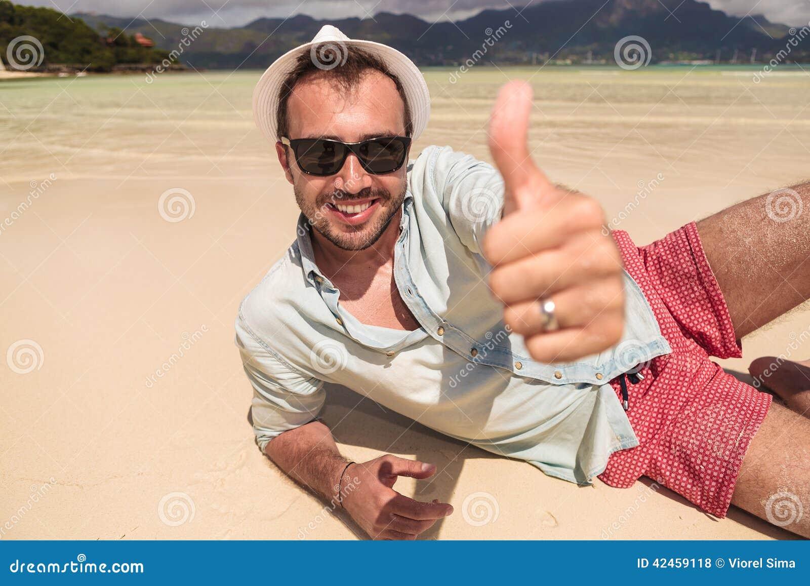 Bemannen Sie das Lügen auf Strand und macht das okayzeichen