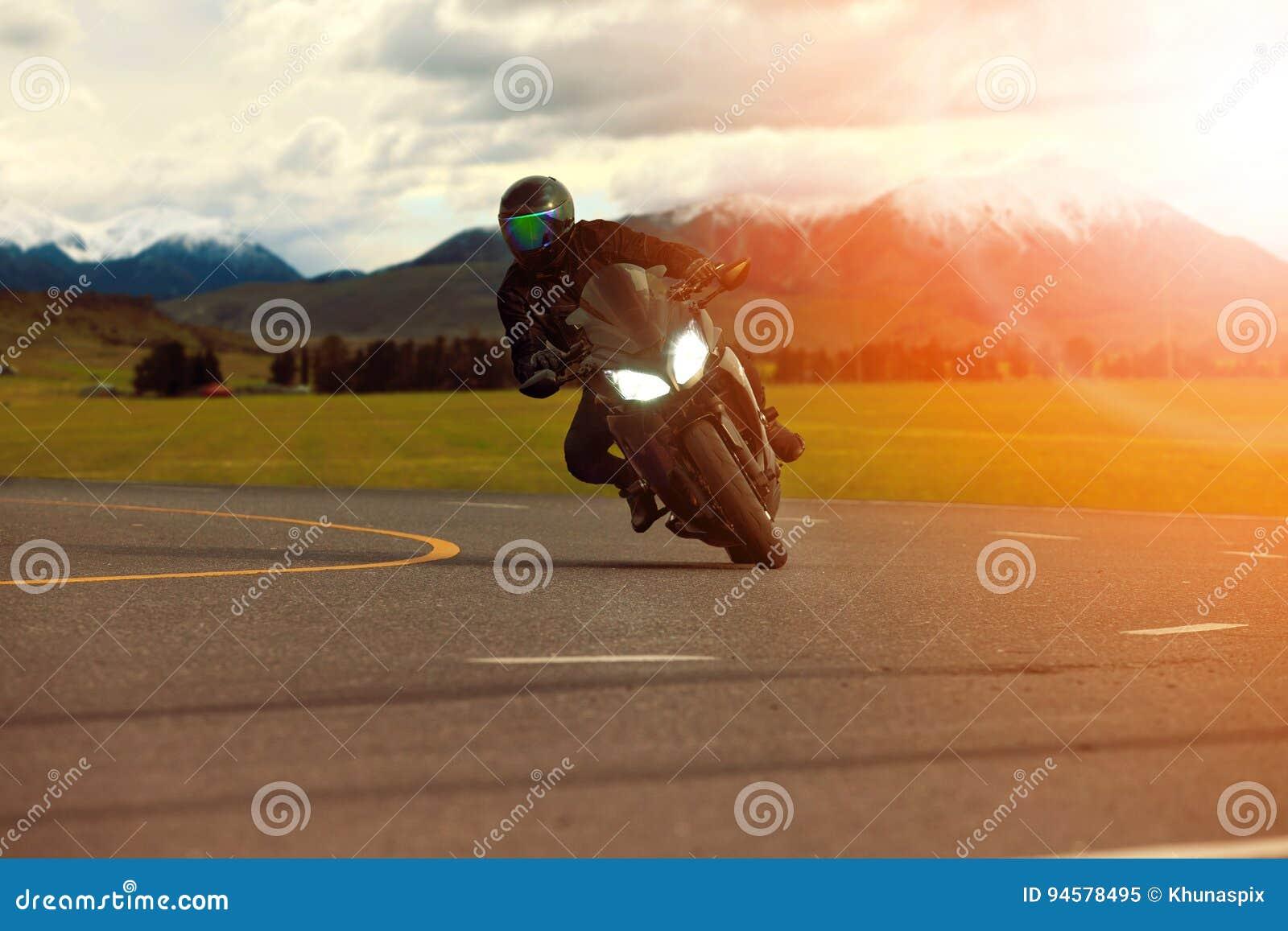 Bemannen Sie das Reitsportmotorrad, das in der scharfen Kurve mit travelin sich lehnt