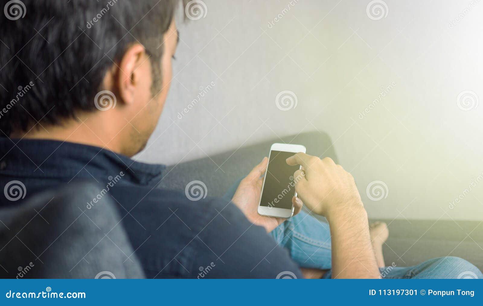 Bemannen Sie das Schieben des Telefons und auf Sofa zu Hause sitzen