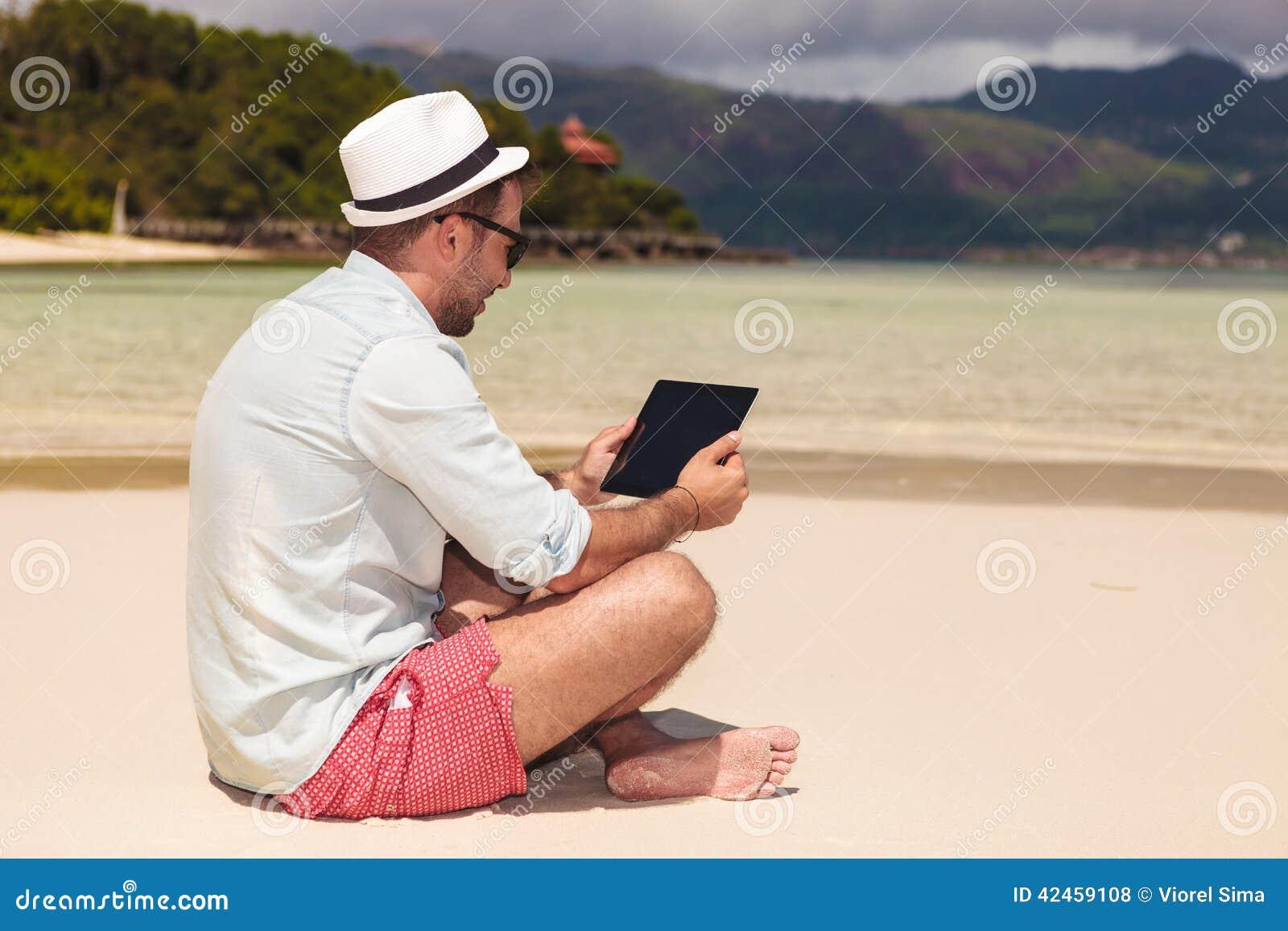 Bemannen Sie das Sitzen auf dem Strand und das Ablesen auf Tablette