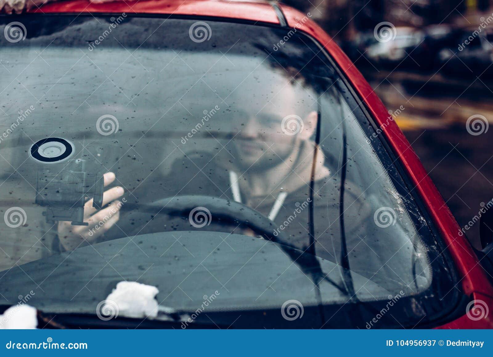 Bemannen Sie den Fahrer, der intelligentes Telefon im Auto, modernes Internet-Technologiekommunikationskonzept verwendet