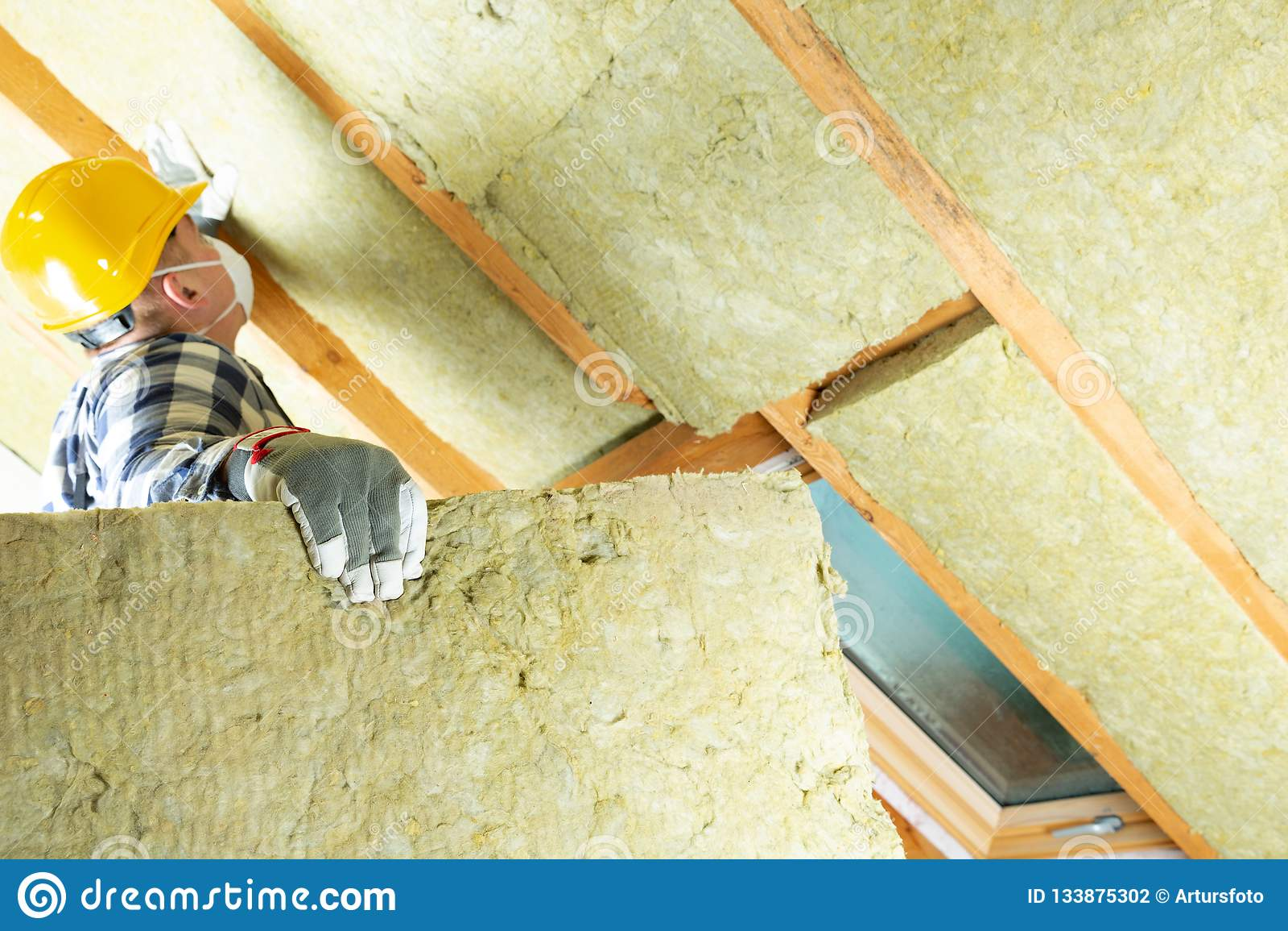 Bemannen Sie die Installierung der thermischen Dachdämmschicht - unter Verwendung des Minerals flehen Sie an