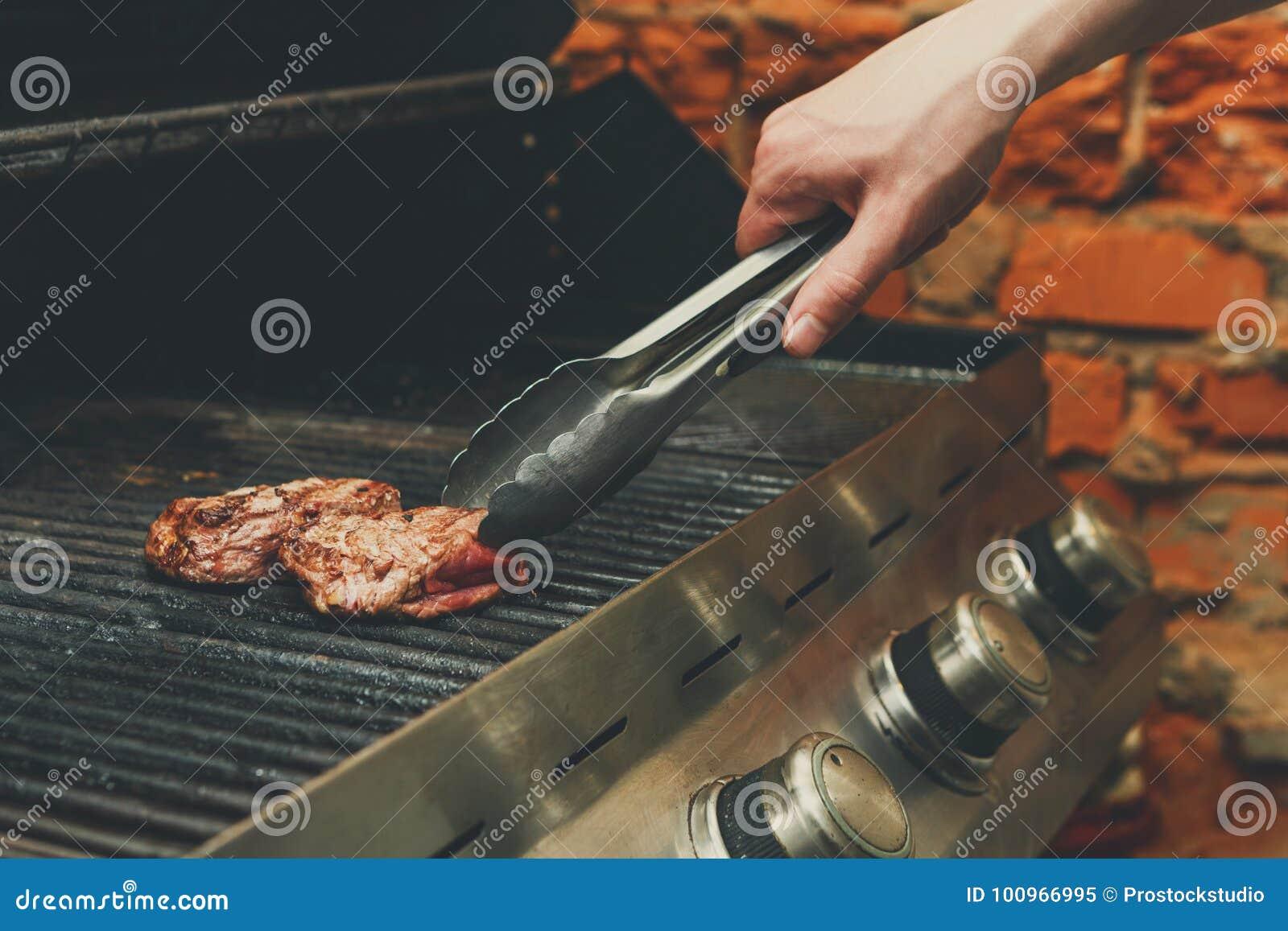 Bemannen Sie Fleischsteaks auf Berufsgrill draußen kochen
