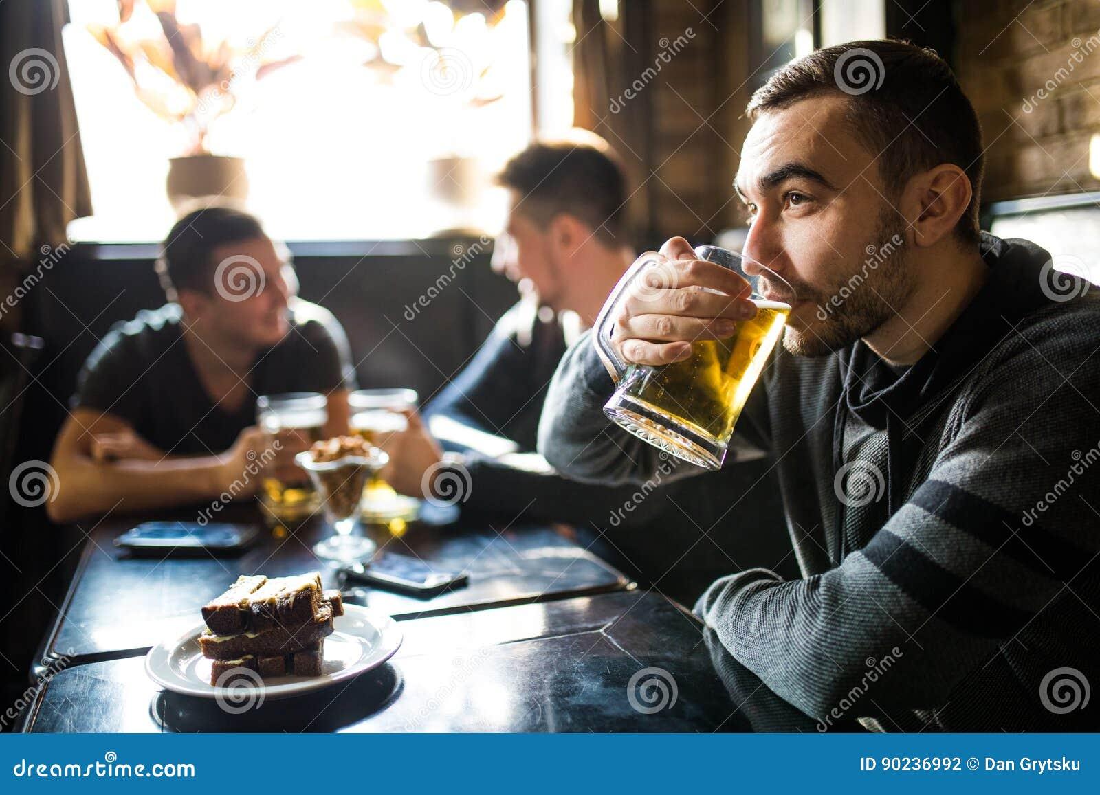 Bemannen Sie Getränkbier vor zur Diskussion, Freunde trinkend in der Kneipe Freunde in der Kneipe
