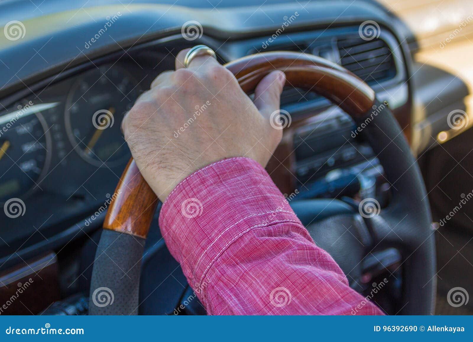 Bemannen sie ` s hand auf dem lenkrad innerhalb eines autos