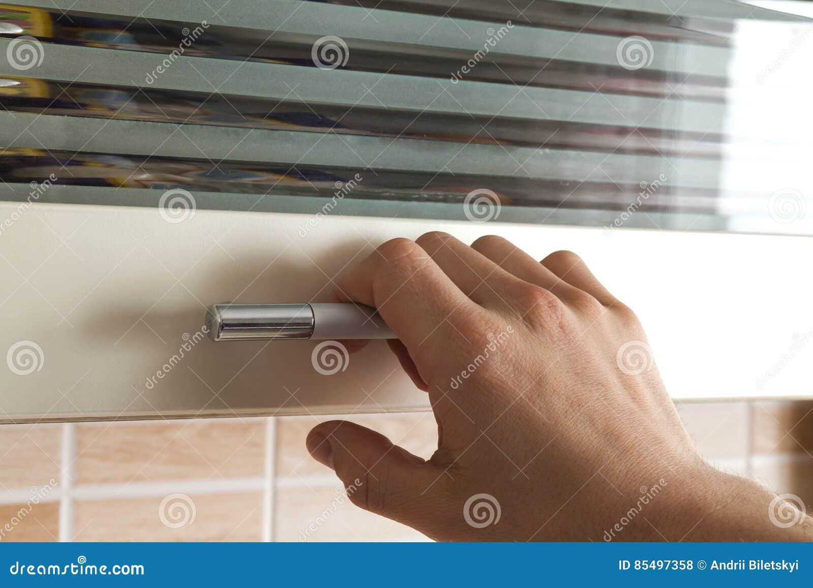 bemannt hand eröffnen die küchenschranktüren, abschluss stockfoto
