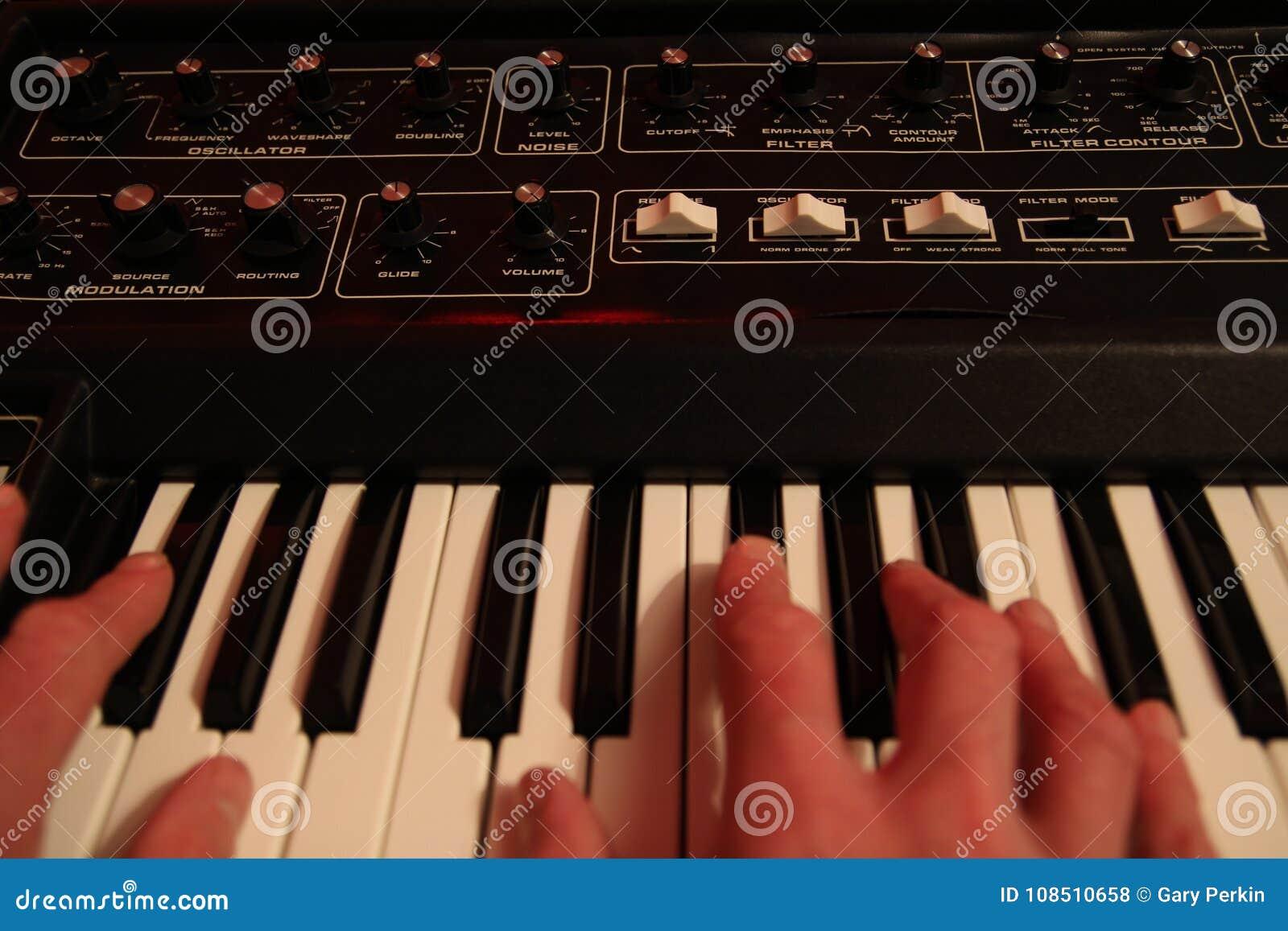 Bemant handen spelend een uitstekend retro analogon synth