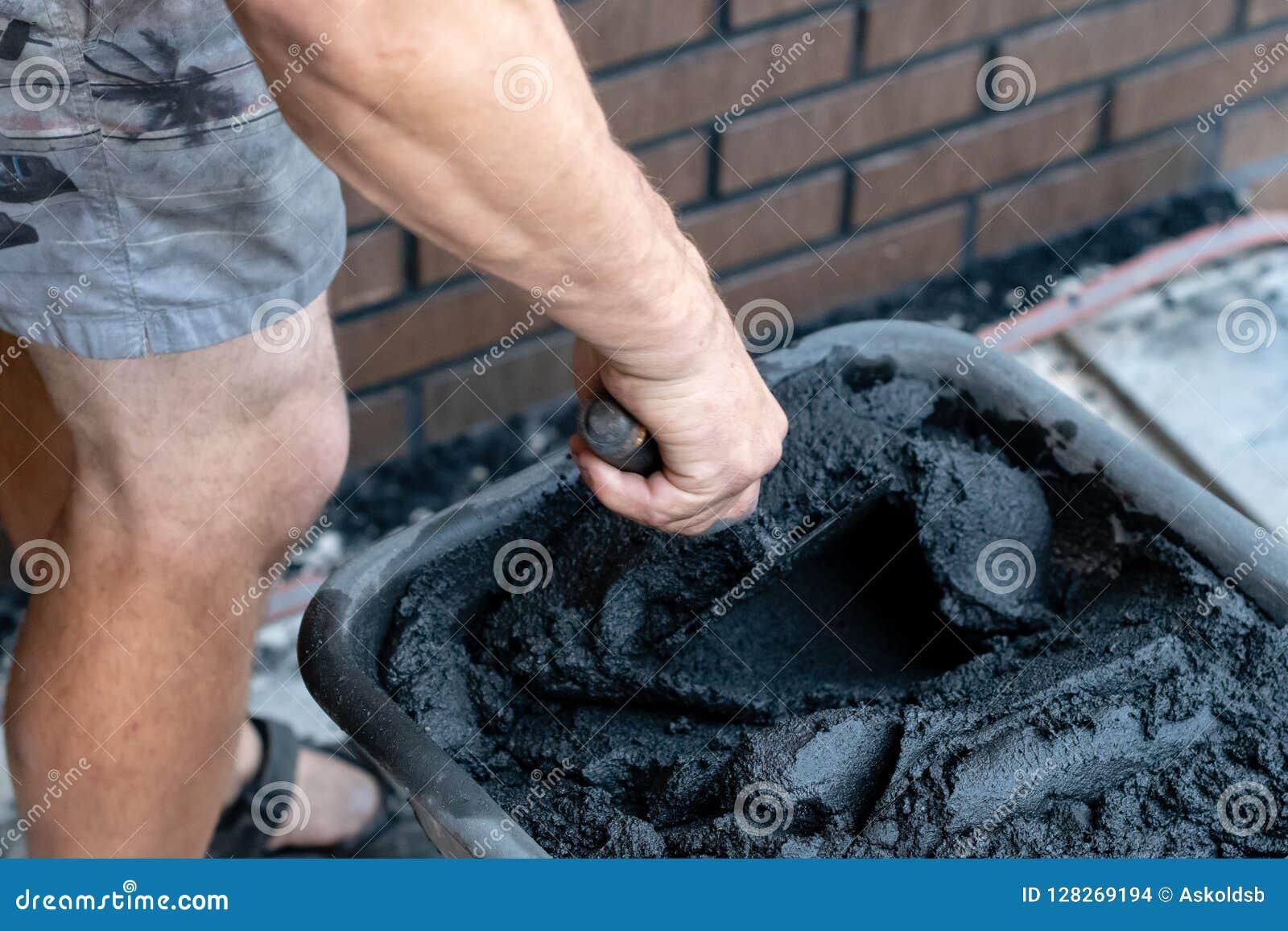 Bemant handgreep een troffel en een gemengd cement in emmer