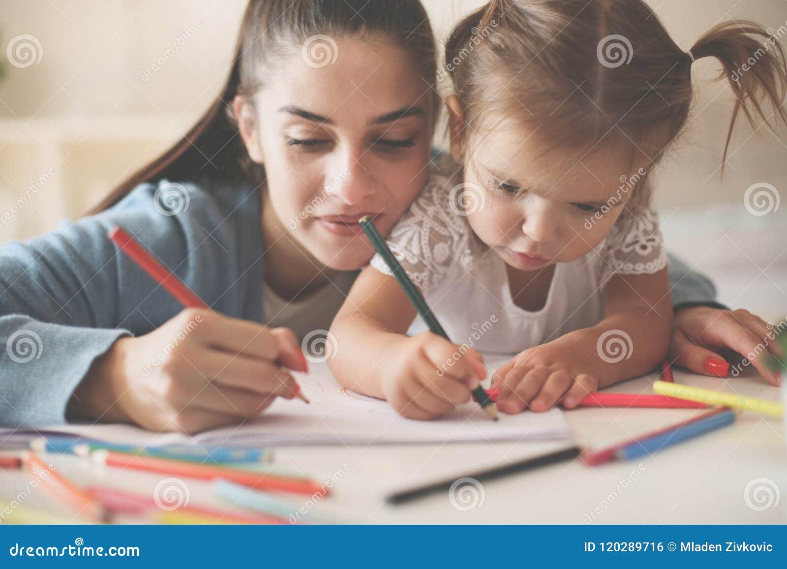 Bemuttern Sie das Helfen ihres kleinen Mädchens zu zu Hause schreiben