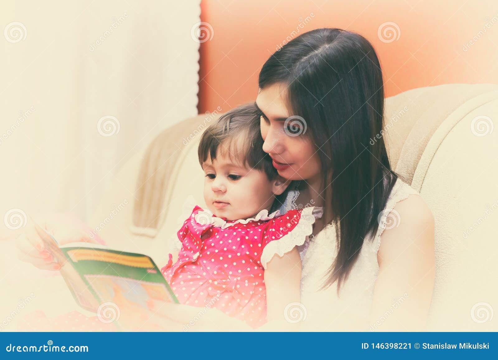 Bemuttern Sie das Lesen eines Buches mit ihrer kleinen Tochter