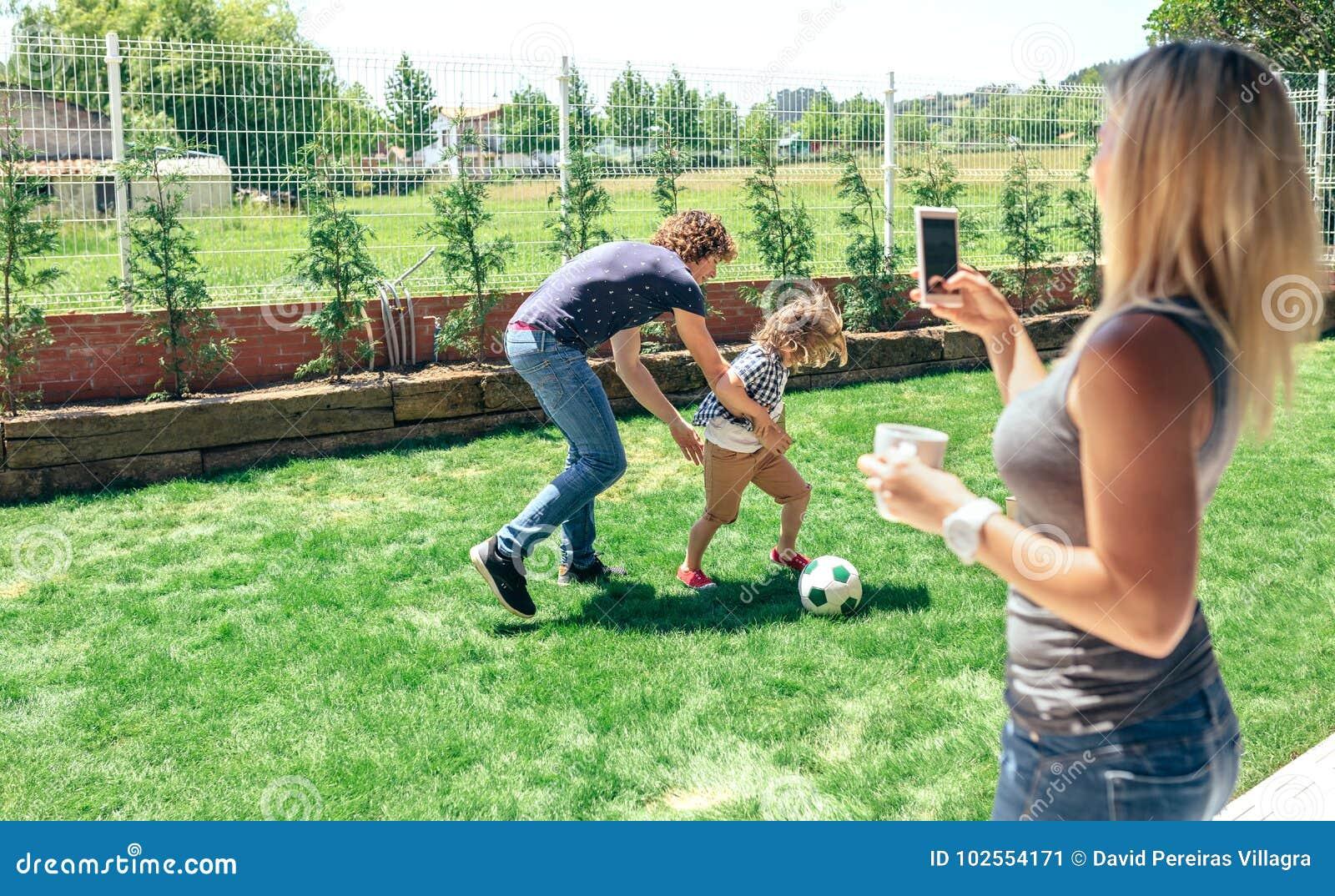 Bemuttern Sie das Machen des Fotos ihres Ehemann- und Sohnspielens