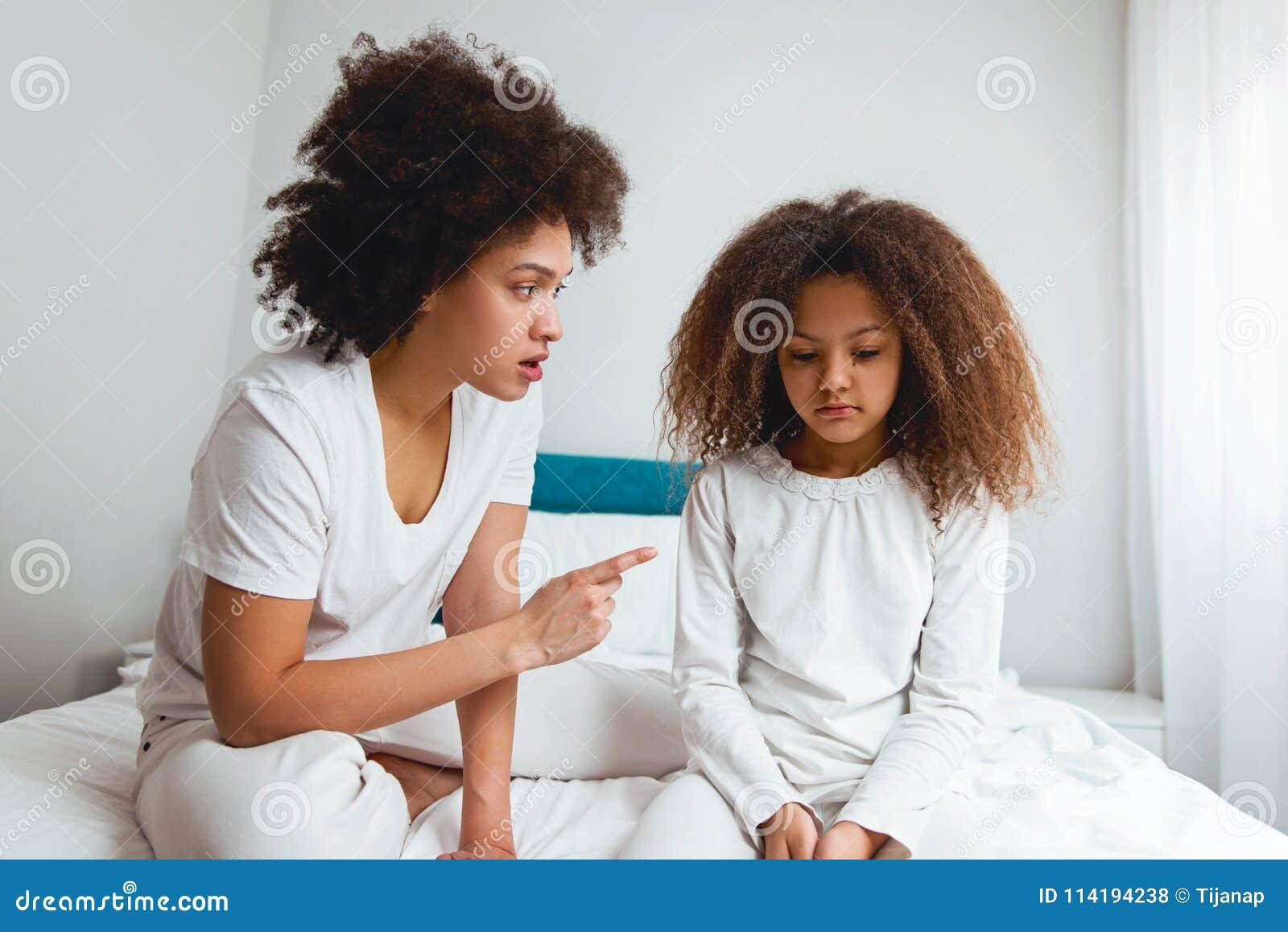 Bemuttern Sie das Schelten ihrer Tochter und im Schlafzimmer sitzen