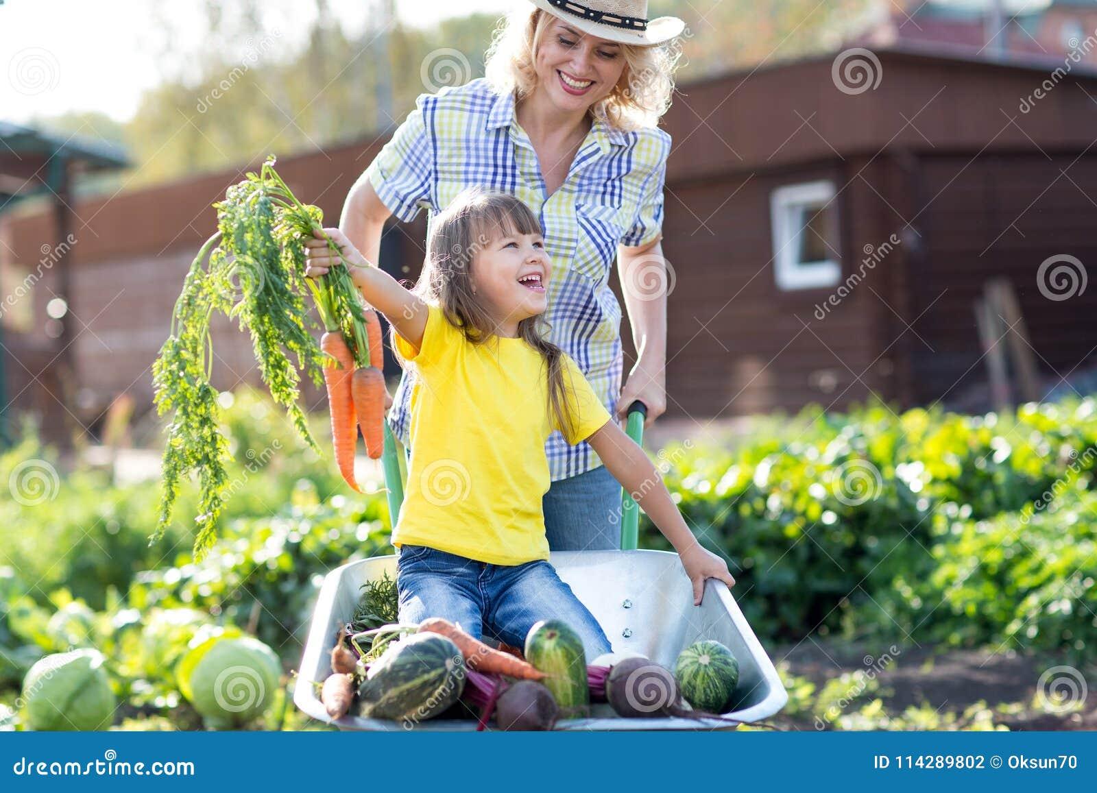 Bemuttern Sie das Spielen mit Kind im Garten im Dorf