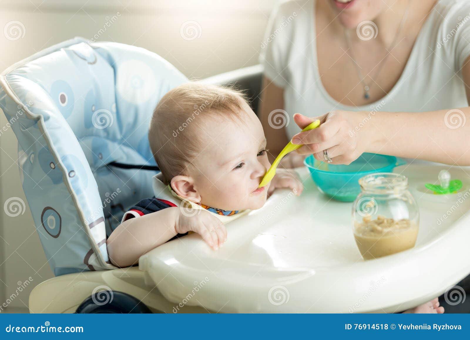 Bemuttern Sie die Fütterung ihrer 9 Monate alten Babysohns, die im Kinderstuhl sitzen