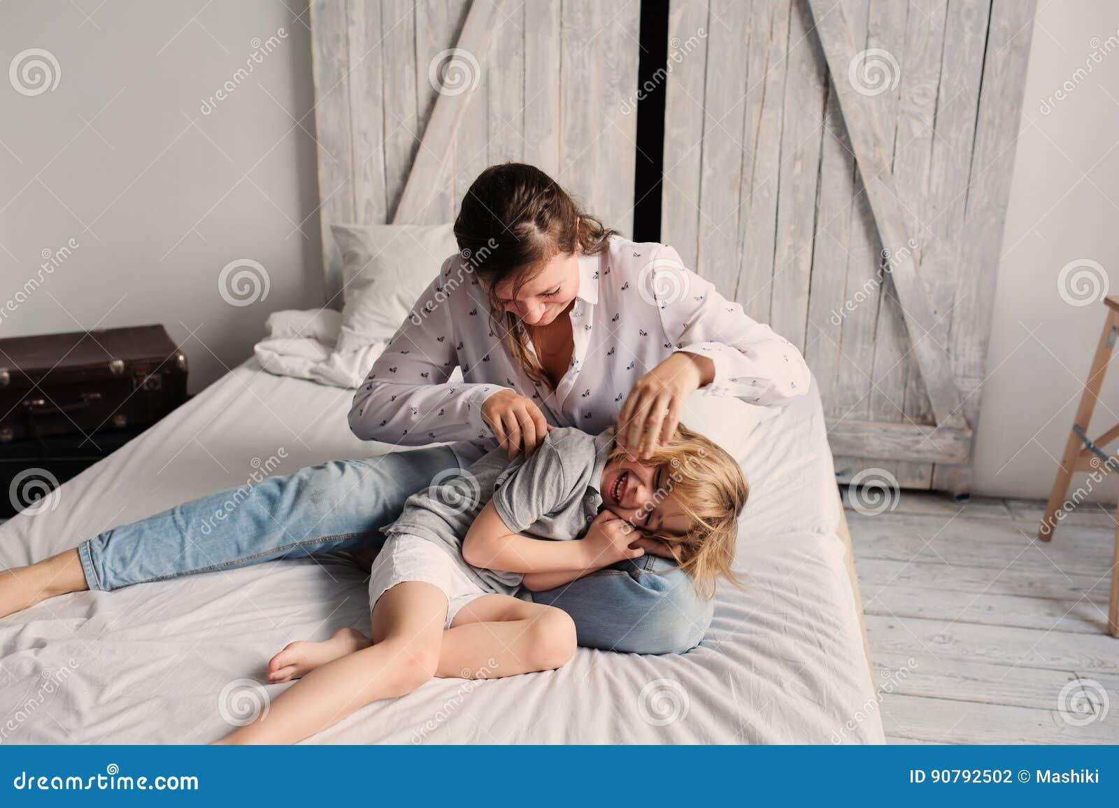 Bemuttern Sie mit Kindersohn auf Bett morgens spielen