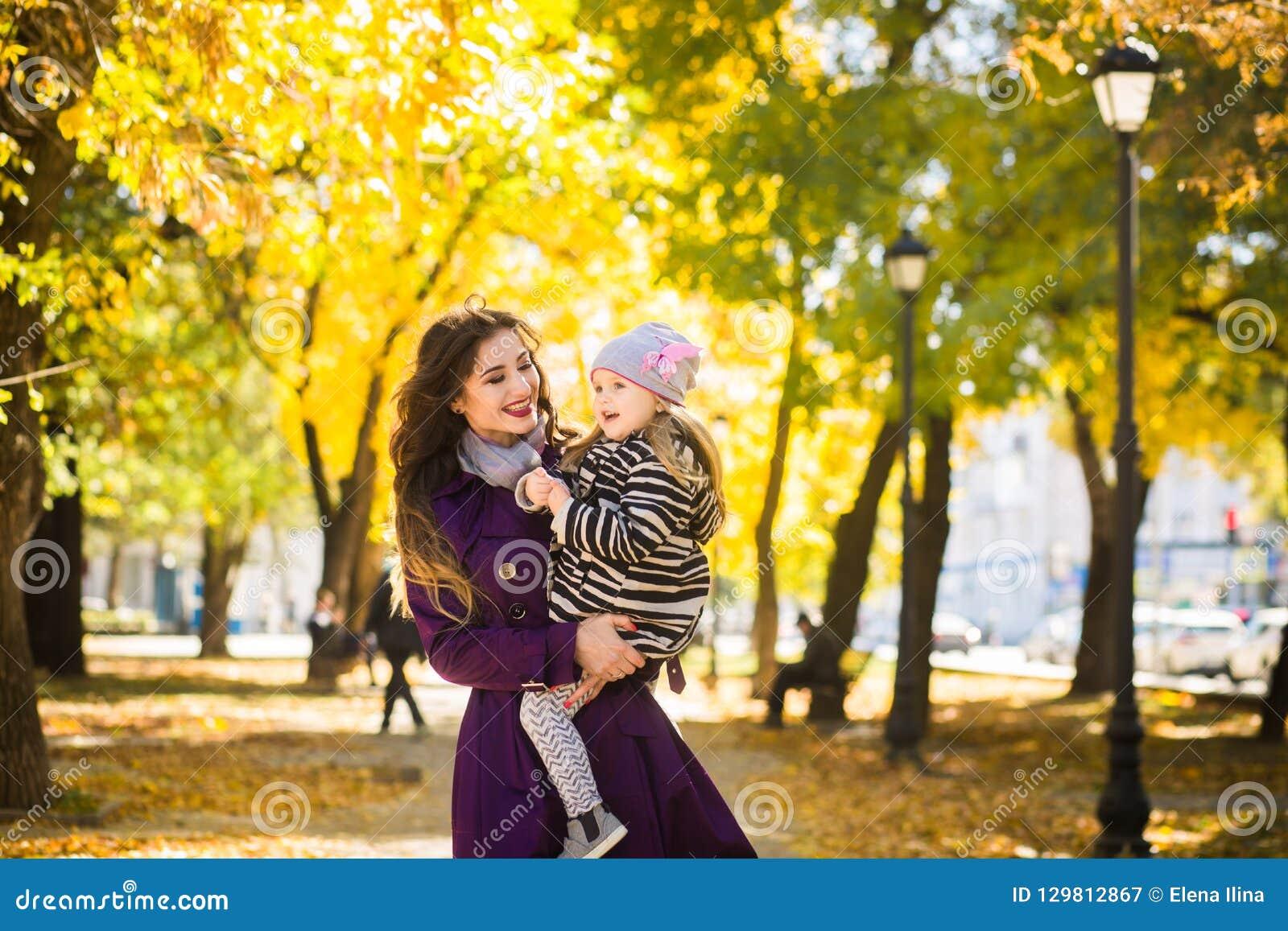 Bemuttern Sie und ihr Kindermädchen, das zusammen draußen auf Herbstweg in der Natur spielt