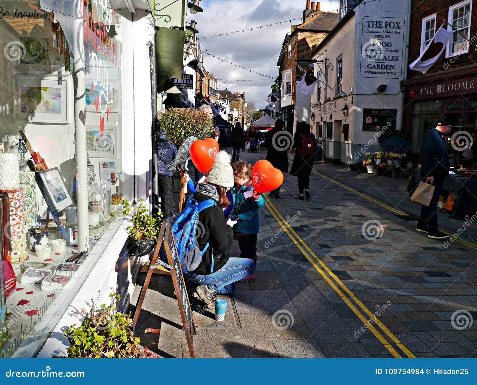 Bemuttern Sie und zwei Kinder, die rote Herzformballone in Twickenham Großbritannien halten