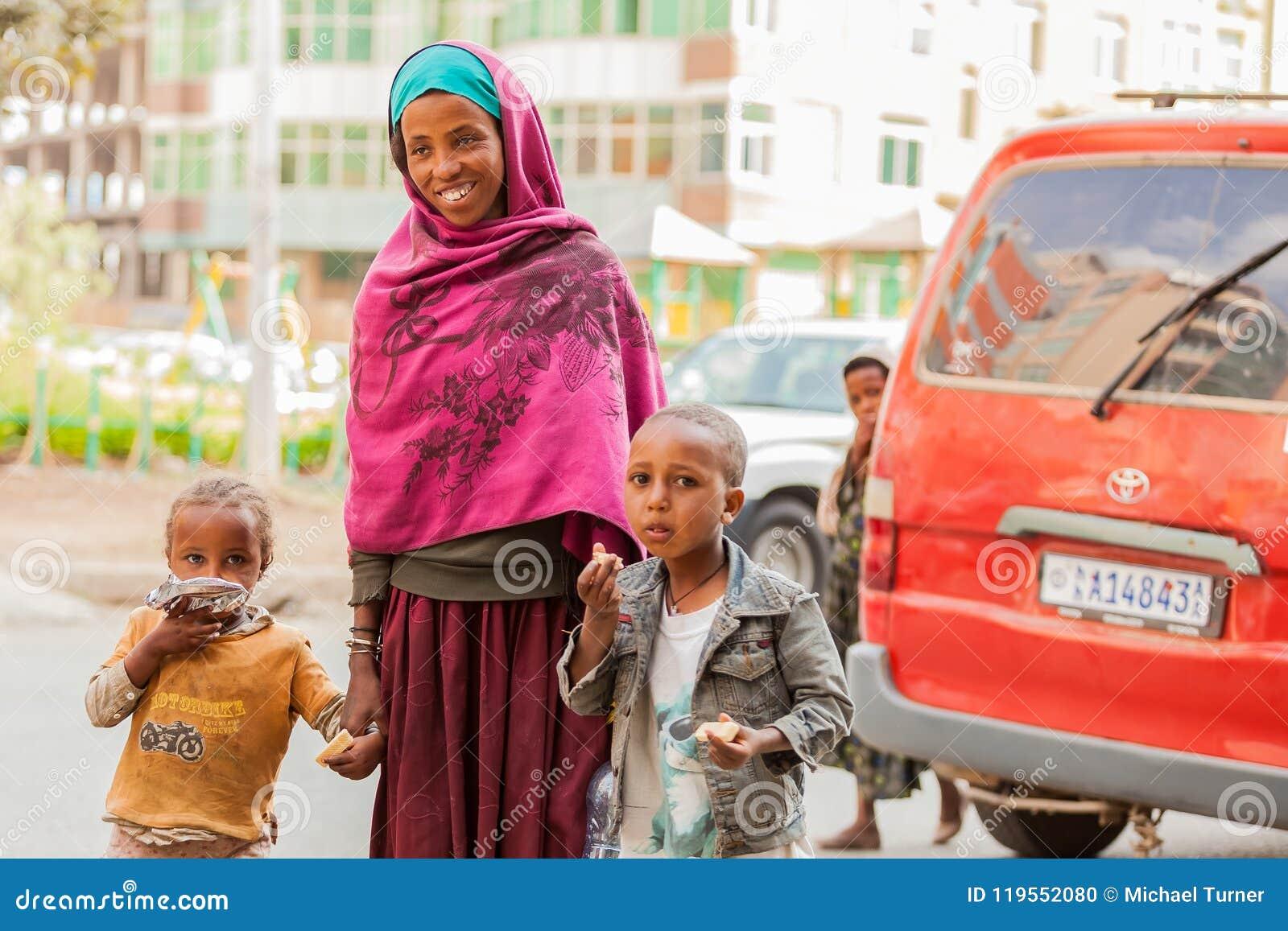 Bemuttern Sie und zwei Kinderhändchenhalten auf einem ruhigen Stadtstraße whi