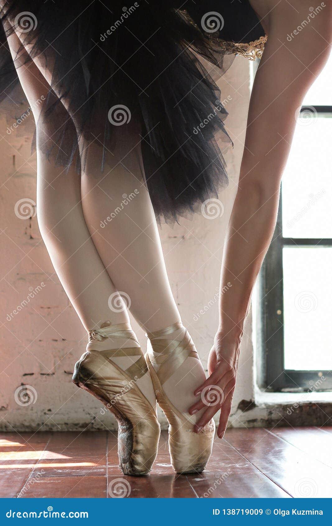 Ben av en ballerinacloseup Benen av en ballerina i gammal pointe Repetitionballerina i korridoren Konturljus från fönstret